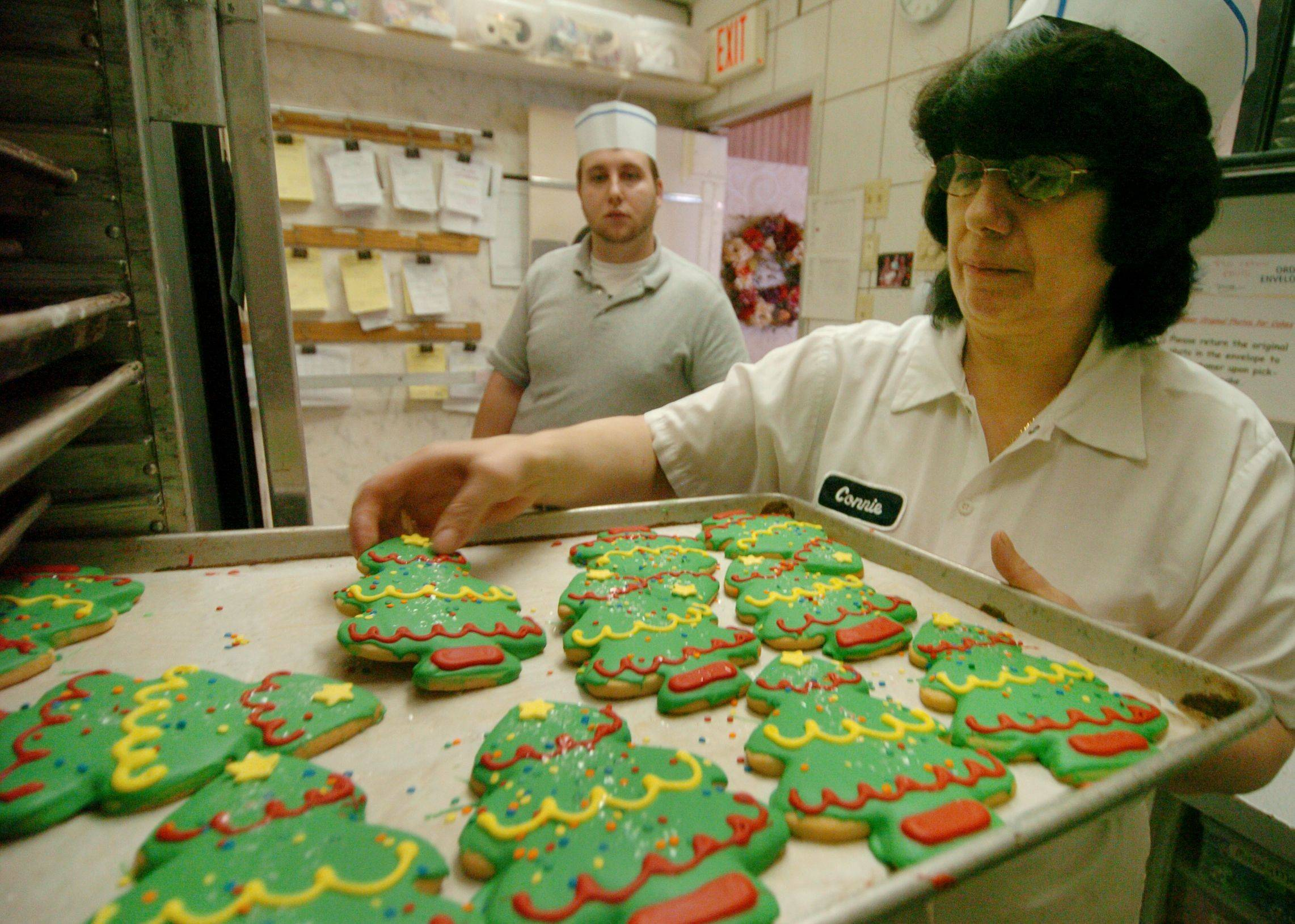 Connie Trakas, general manager of production and 28-year veteran at the bakery, pulls out a rack of Christmas sugar cookies ready to be packed and displayed in the store.