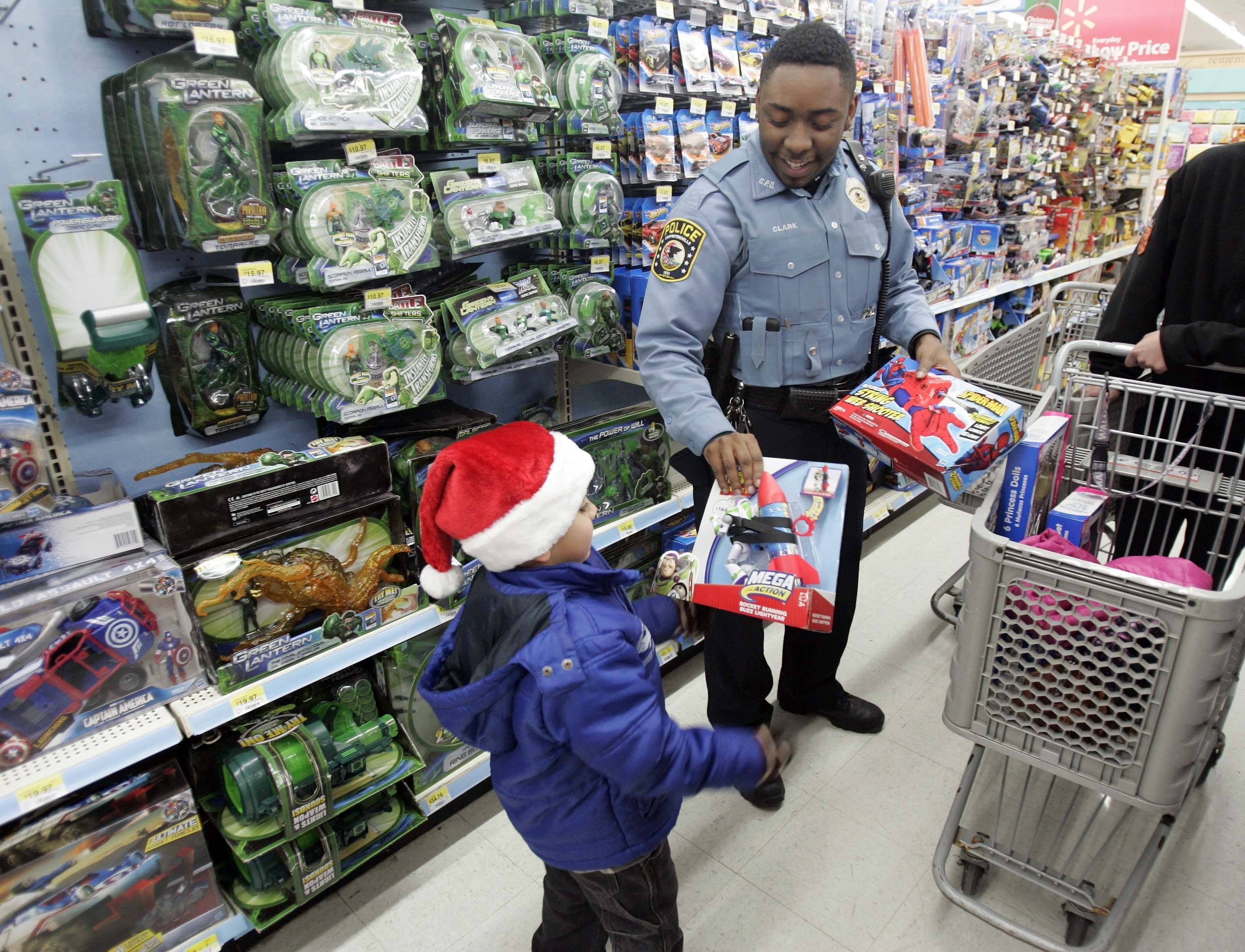 Brian Hill/bhill@dailyherald.com Tony Perez, 4, of Carpentersville, hands Carpentersville Community Service Officer Marcus Clark a gift to add to the basket during Shop with a Cop program Saturday at Wal-Mart in East Dundee.