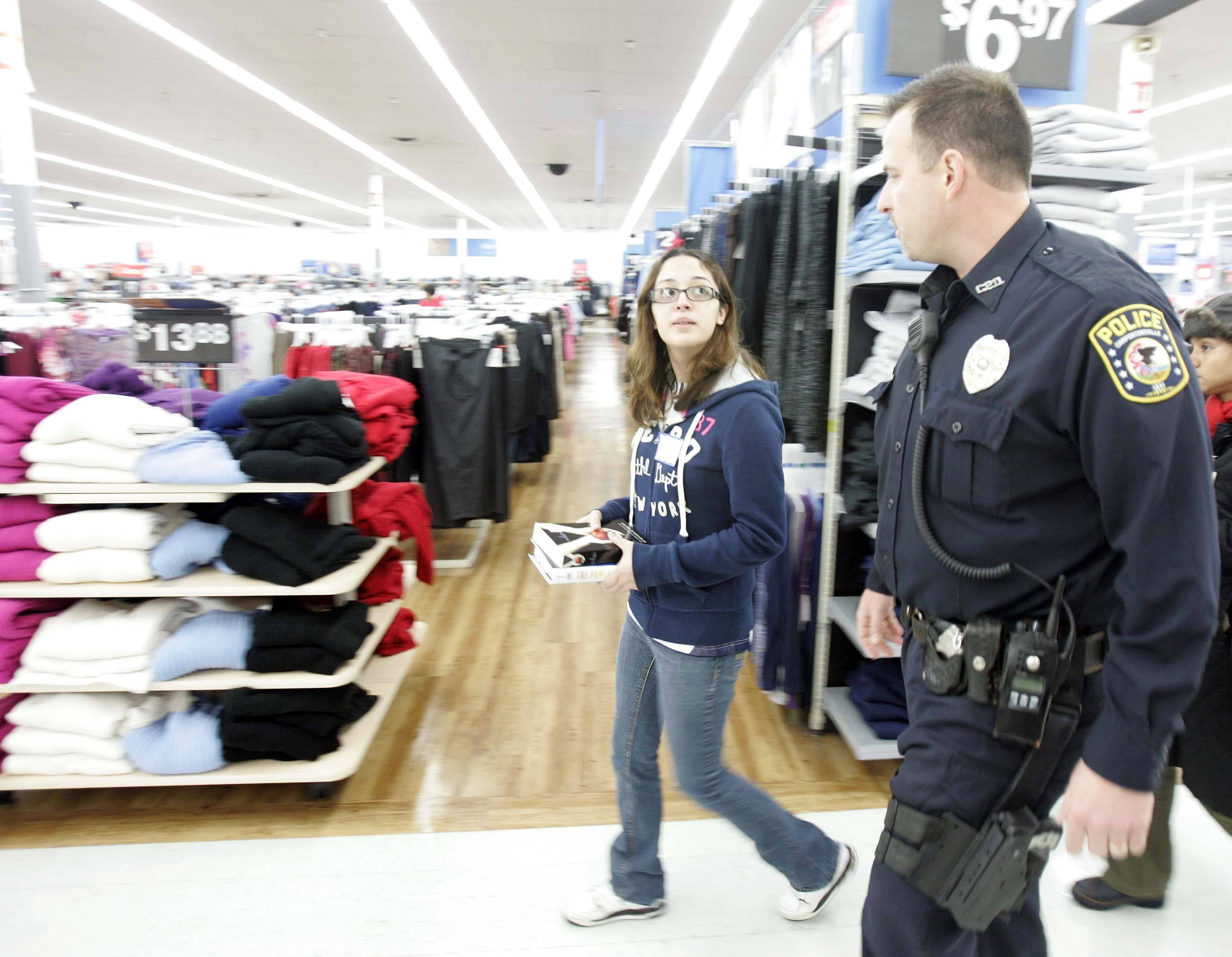 Brian Hill/bhill@dailyherald.comGabriela Vega, 15, of Carpentersville, carries a gift for one of her siblings as she talks to Officer Morgan Brown of Carpentersville during the Shop with a Cop program at Wal-Mart in East Dundee Saturday.