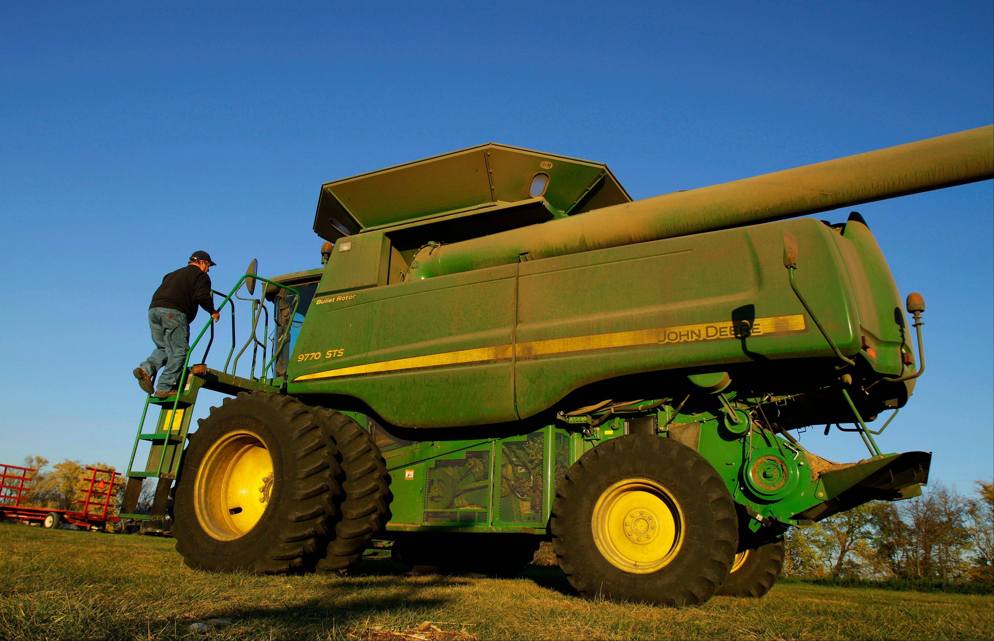 Farmer Dale Hadden climbs onto a combine on the family farm near Jacksonville, Ill. Hadden's farming operation is doing especially well this year for any of a number of reasons and will use this as an opportunity to funnel some of these profits into new machinery and paying off some land.