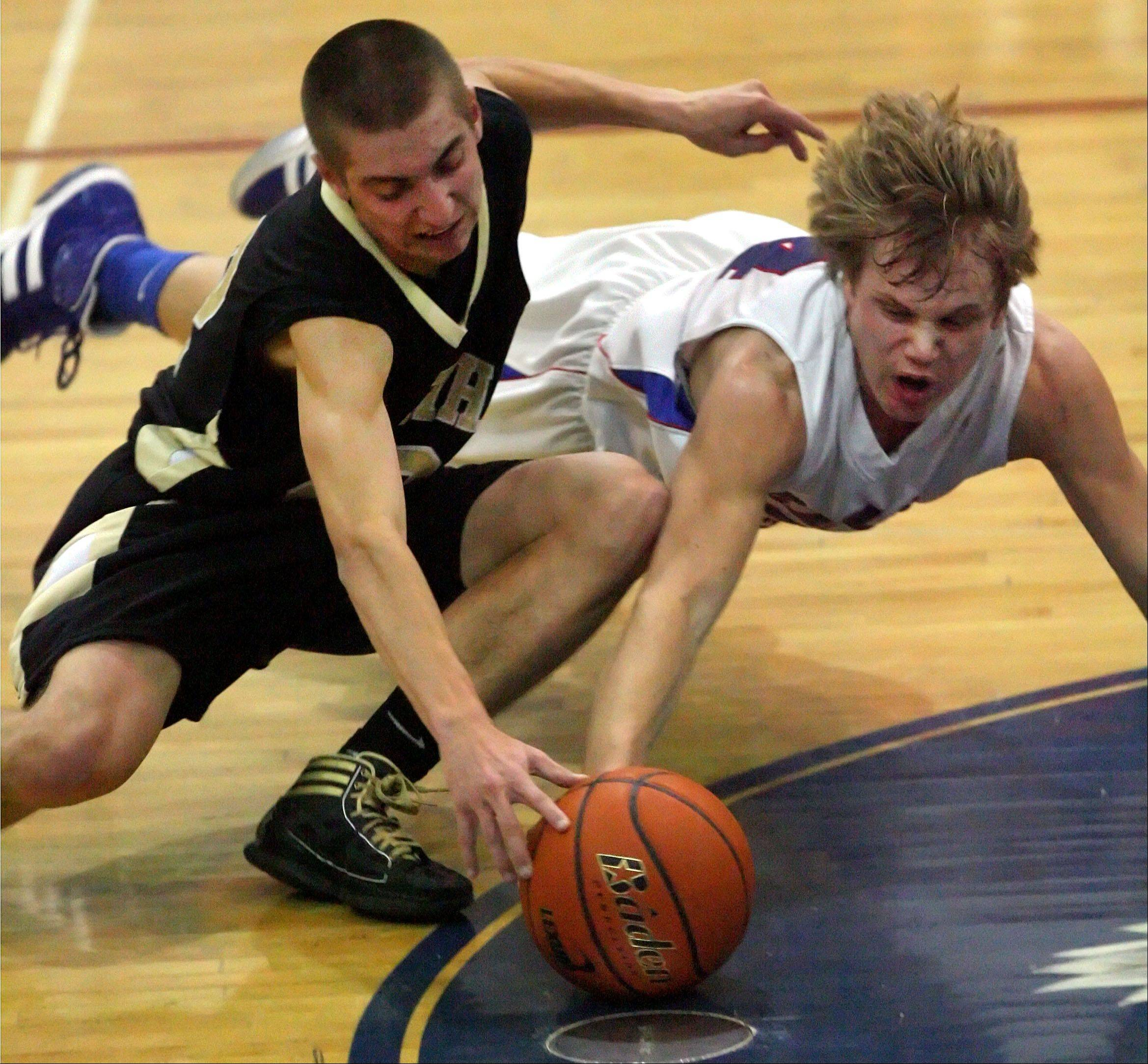 Grayslake North's Danny Mateling, left, and Lakes' Justin Bergeron battle for a loose ball during their game Tuesday night in Lake Villa.