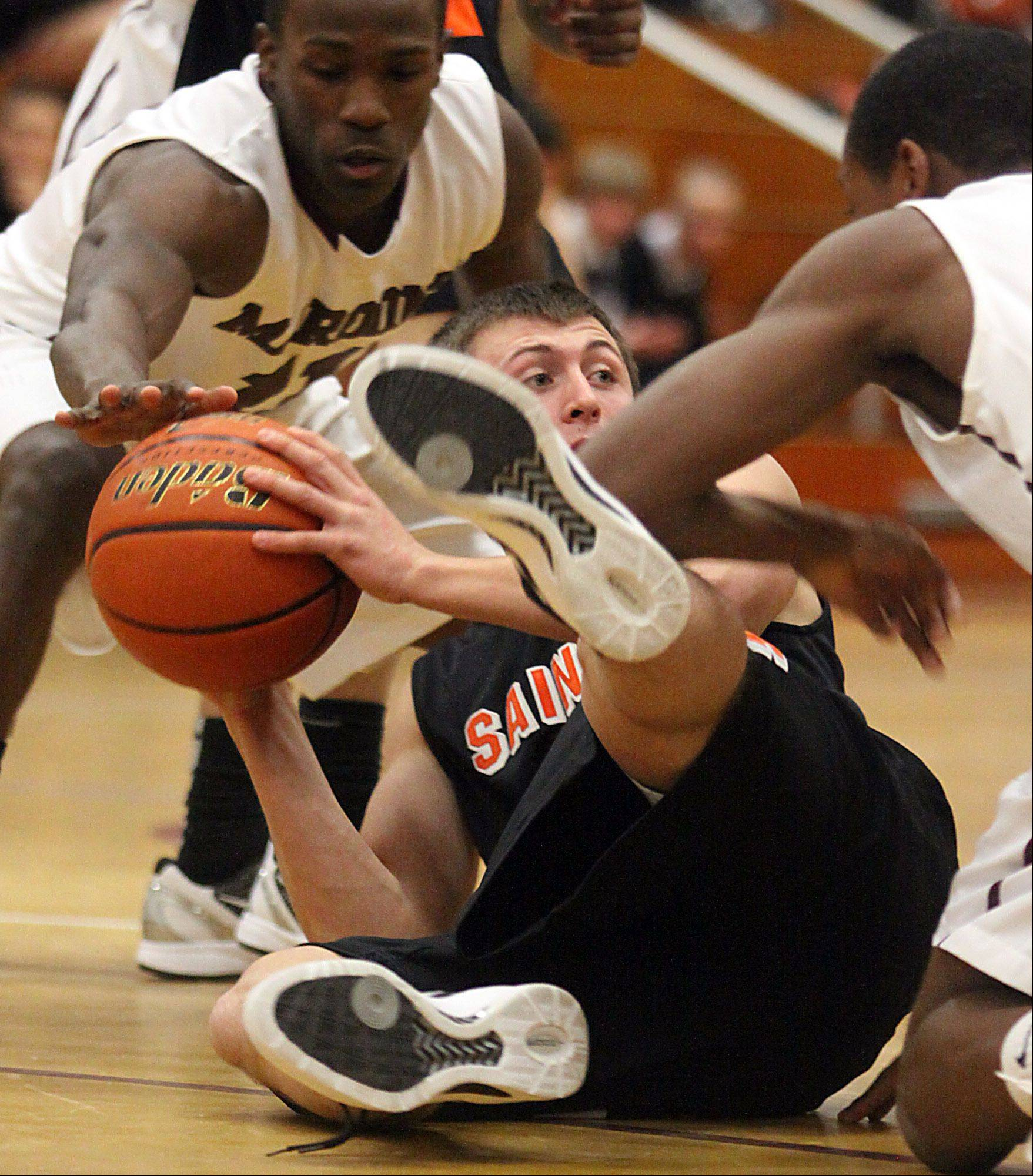 St. Charles East's Charlie Fisher, center, tries to escape Elgin's Dennis Moore, left, and Kory Brown during Friday's basketball game at Chesbrough Fieldhouse in Elgin.