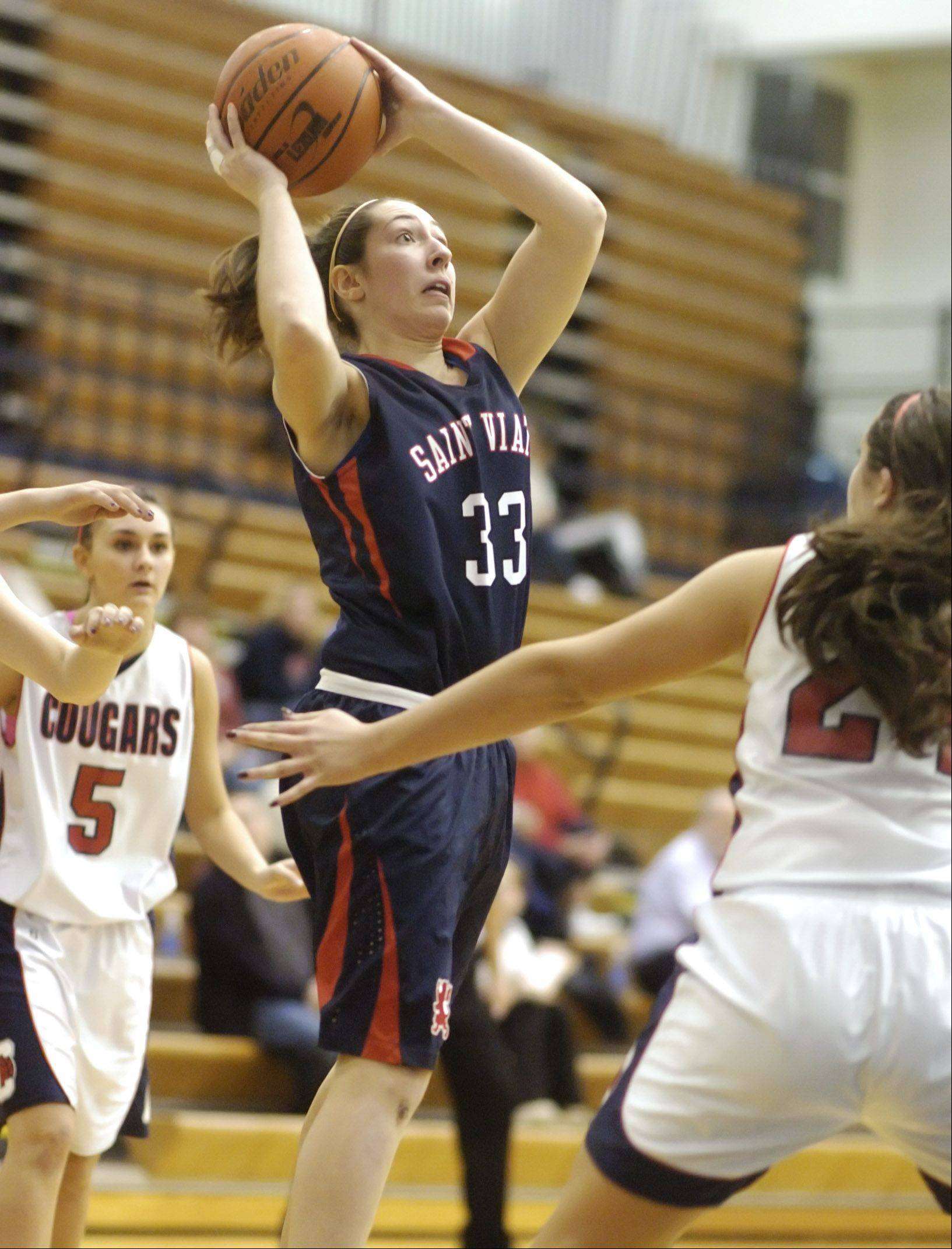 St. Viator's Morgan Hess takes a shot over Conant's Natalie Kutrumanes, right, during Tuesday's basketball game in Hoffman Estates.