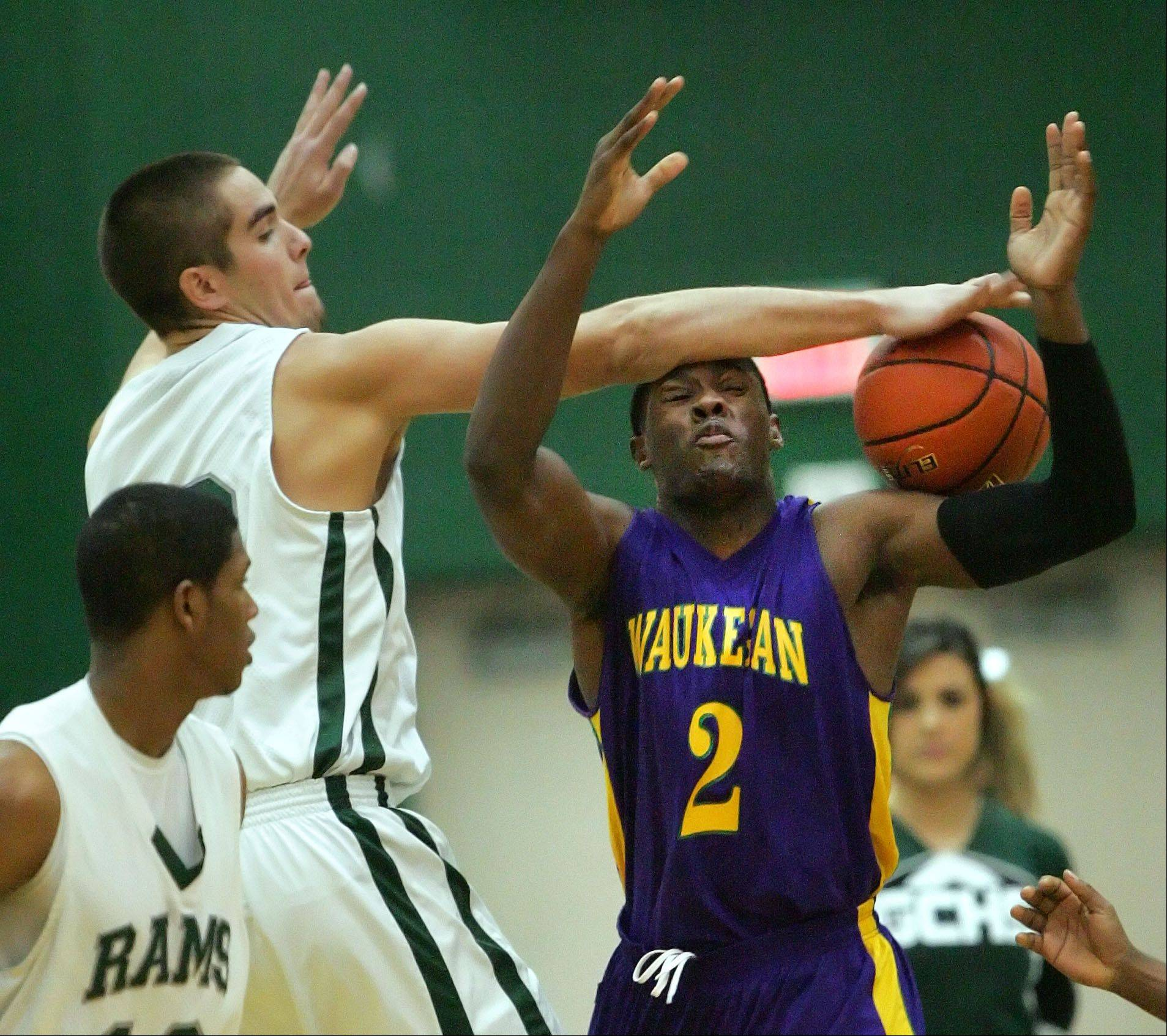 Grayslake Central's Casey Boyle, left, blocks the shot of Waukegan's Akeem Springs during Wednesday's basketball game in Grayslake.