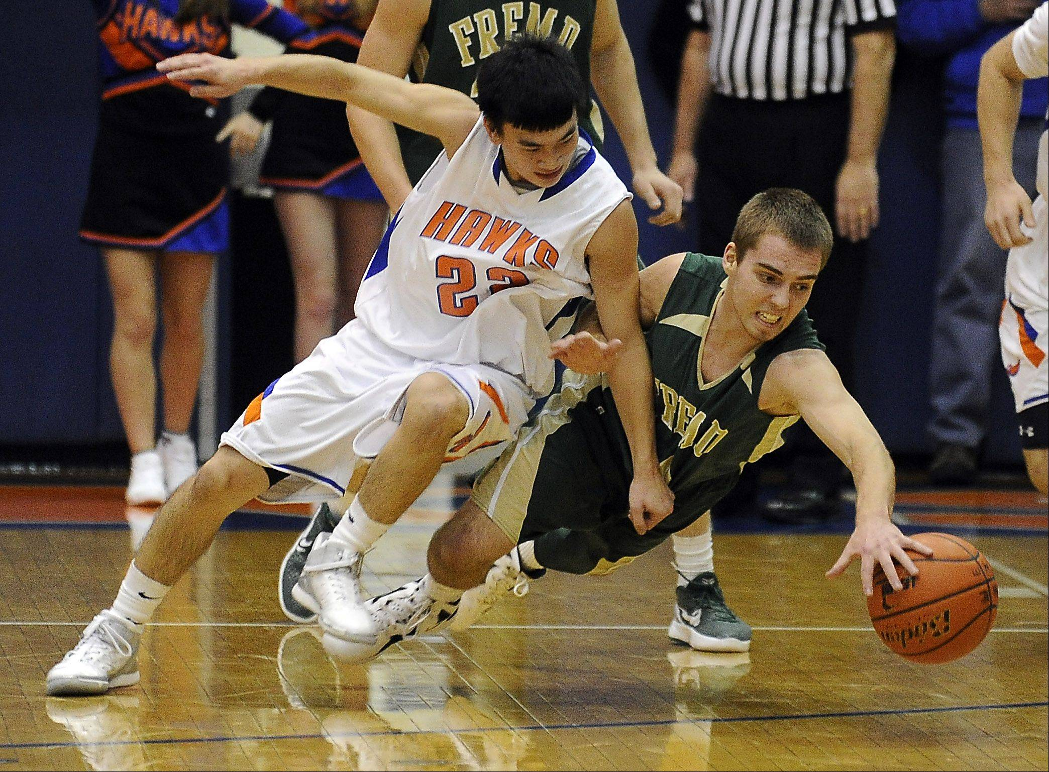 Hoffman Estates' Takuro Azumaya battles Fremd's Jack Nelson for control during Friday's basketball game in Hoffman Estates.