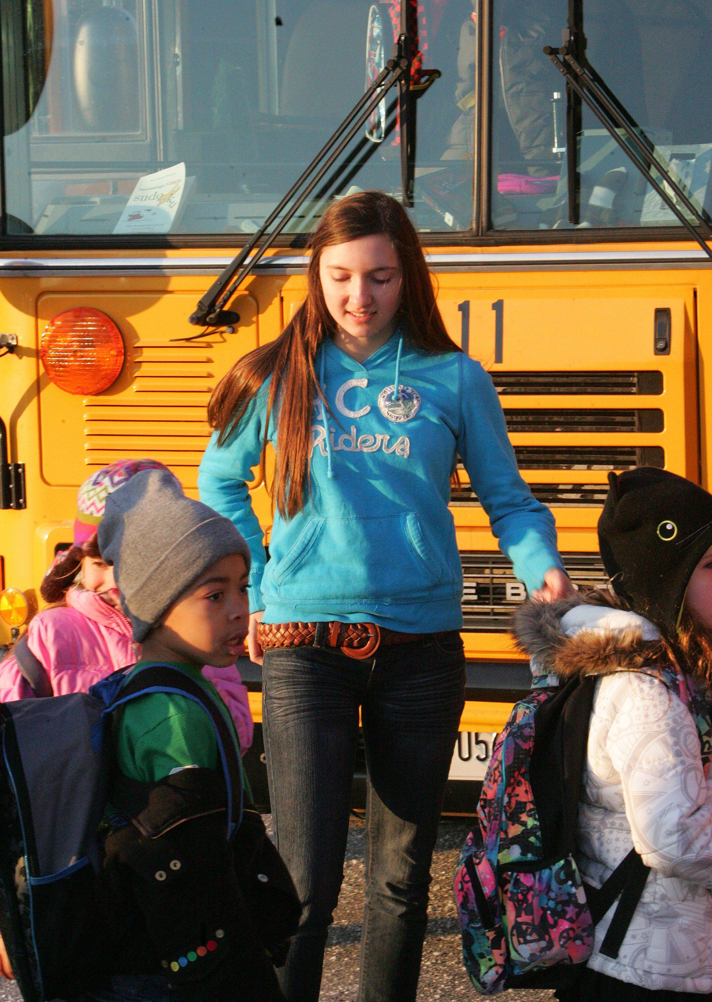 Eighth-grader Diana Guliyeva helps kids get on the bus at Fremont School District 79. Eighth-graders at Fremeont Middle School ride as patrol guards on buses for kindergarten through fifth-grade students.