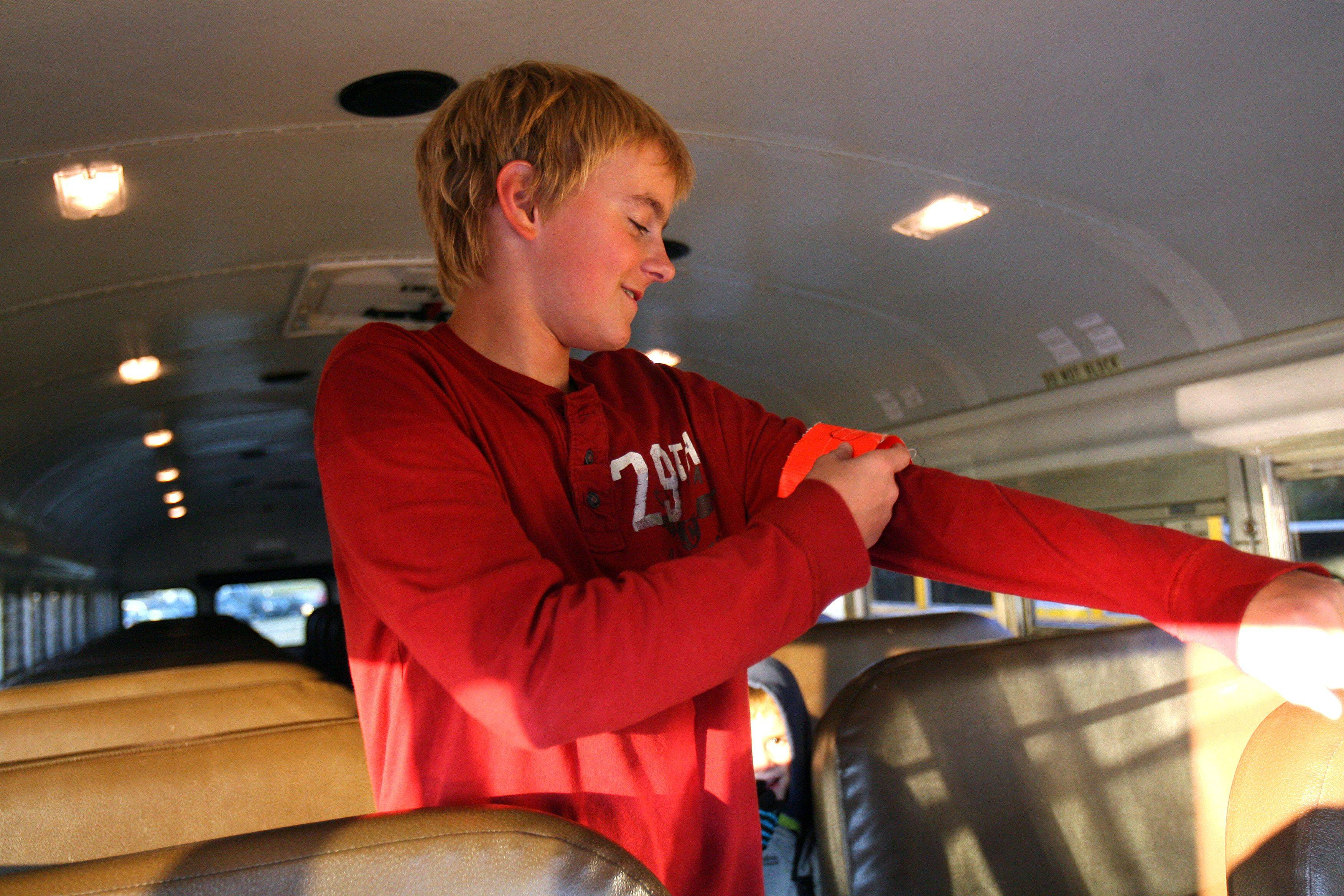 Eighth-grader Trevor Fox puts on his bus patrol arm band. Fremont School District 79 has implemented a program where eighth-graders ride along on buses carrying kindergarten through fifth-graders to help the bus drivers.