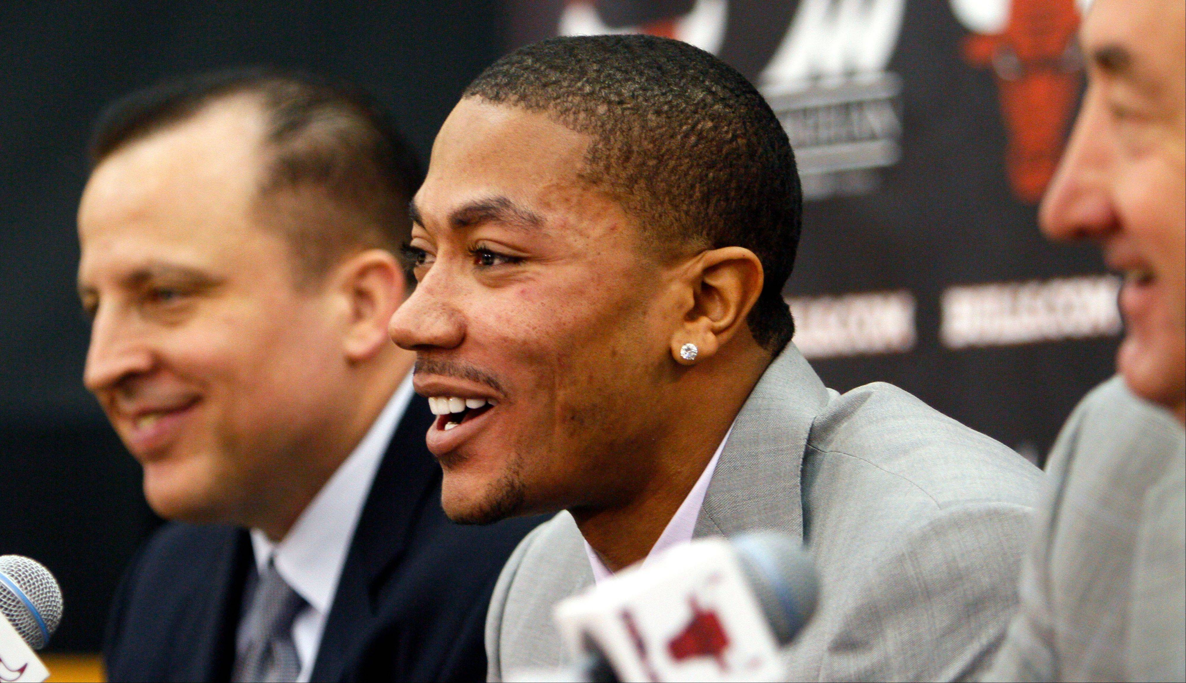 Reigning MVP Derrick Rose, smiles during a news conference flanked by Bulls coach Tom Thibodeau, left, and general manager Gar Forman on Wednesday announcing Rose's five-year contract extension.