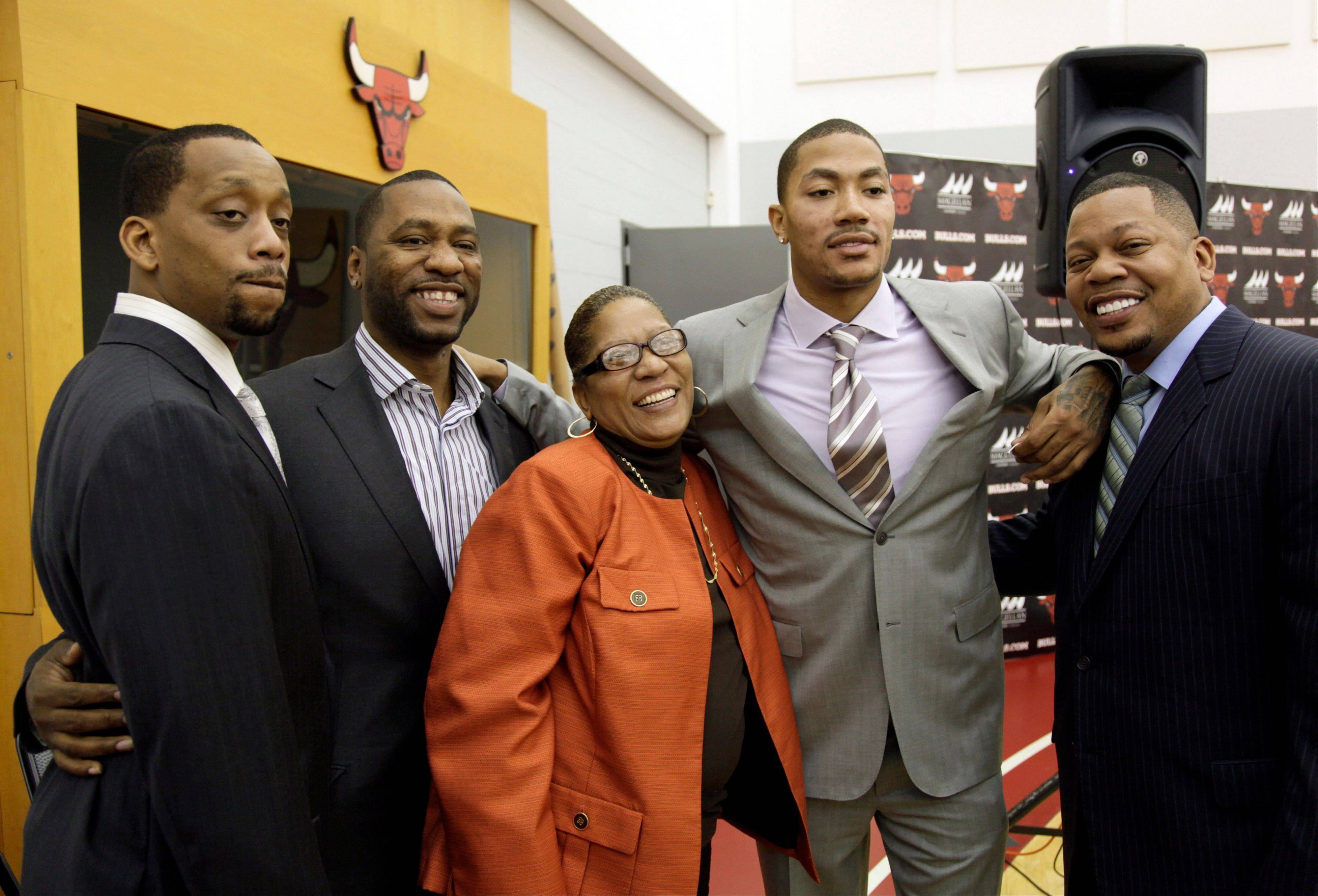 The Bulls' Derrick Rose, second from left, poses for a photo with his brothers Allan, left, Dwayne, second left, Reggie, right, and his mother Brenda after a news conference Wednesday after Rose agreed to a five-year contract extension worth approximately $94 million.