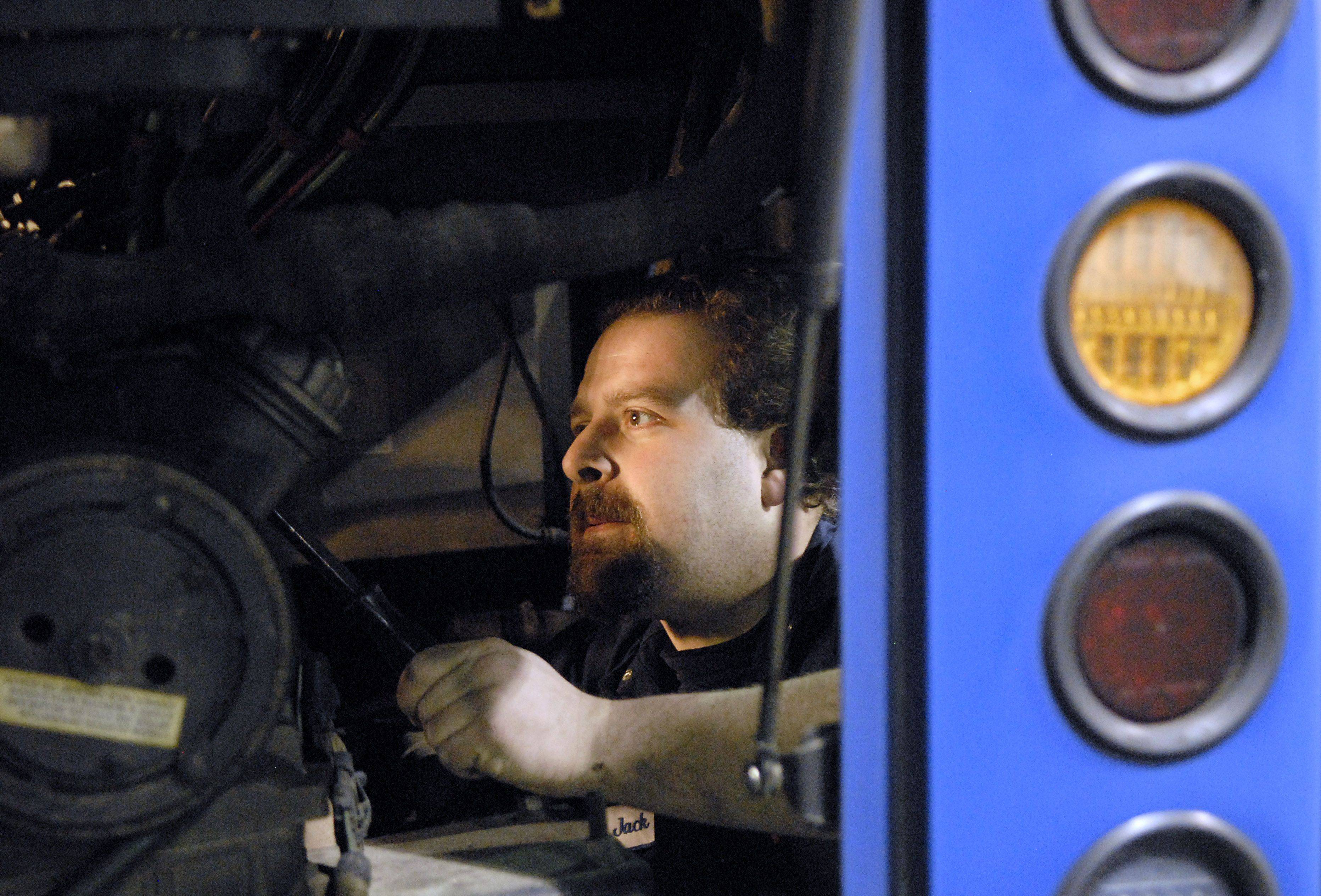Mechanic Jack Rojewski helps out a fellow mechanic working on the engine of a bus. Engines have access panels from the back as well as the side. Rojewksi has been a mechanic for 16 years at Pace.
