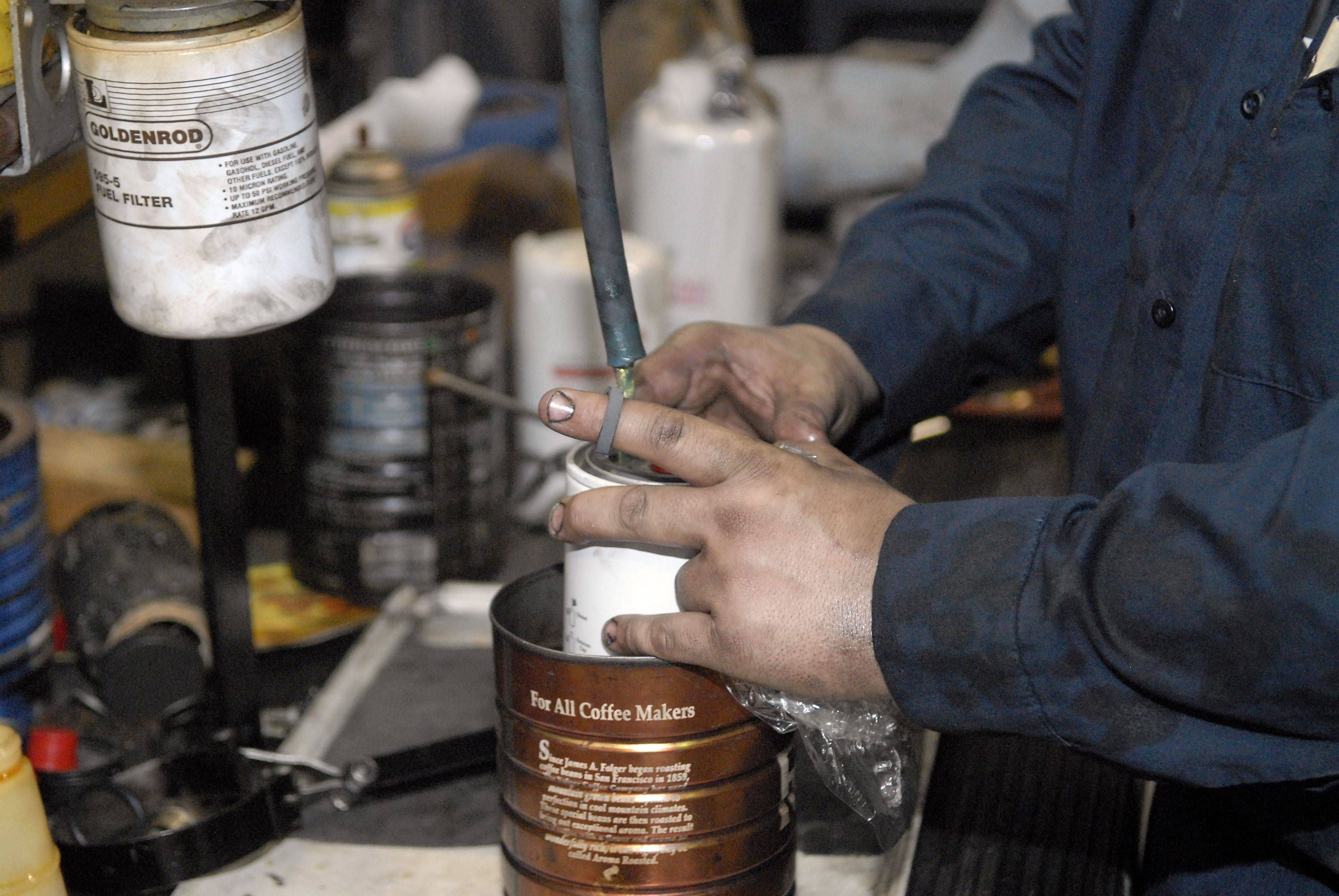 Mechanic Erik Hannig readies a new fuel filter to be placed in a bus at the Elgin garage.
