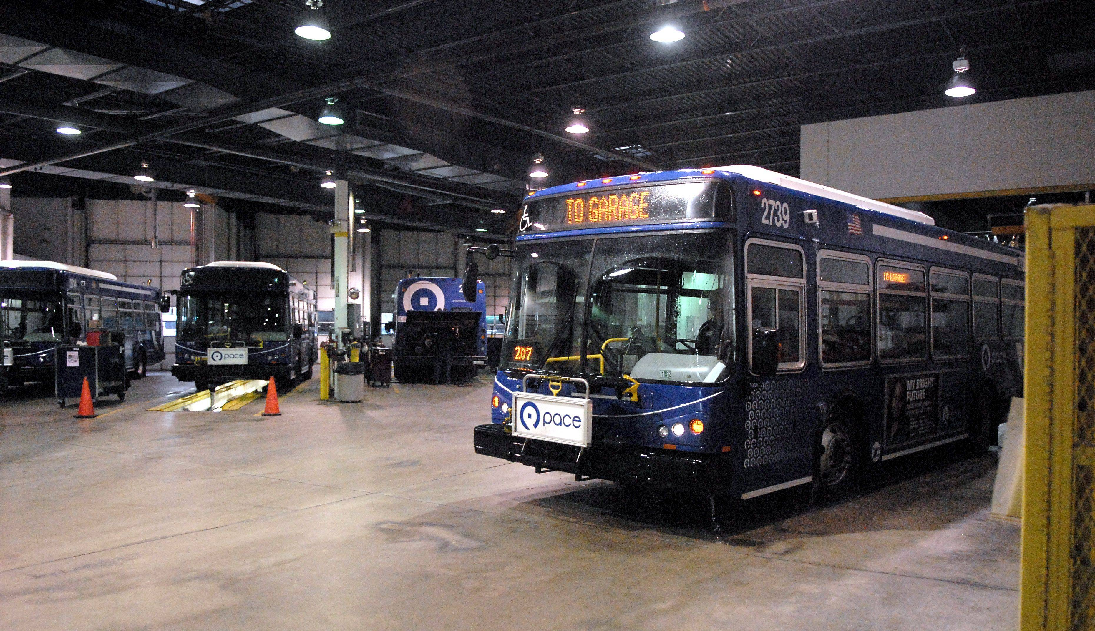 A bus drives out of the washing station past five maintenance bays in the Elgin Pace bus garage. After being refueled, the bus is put through the wash and then parked in the adjoining space ready to go for its next shift in the morning.