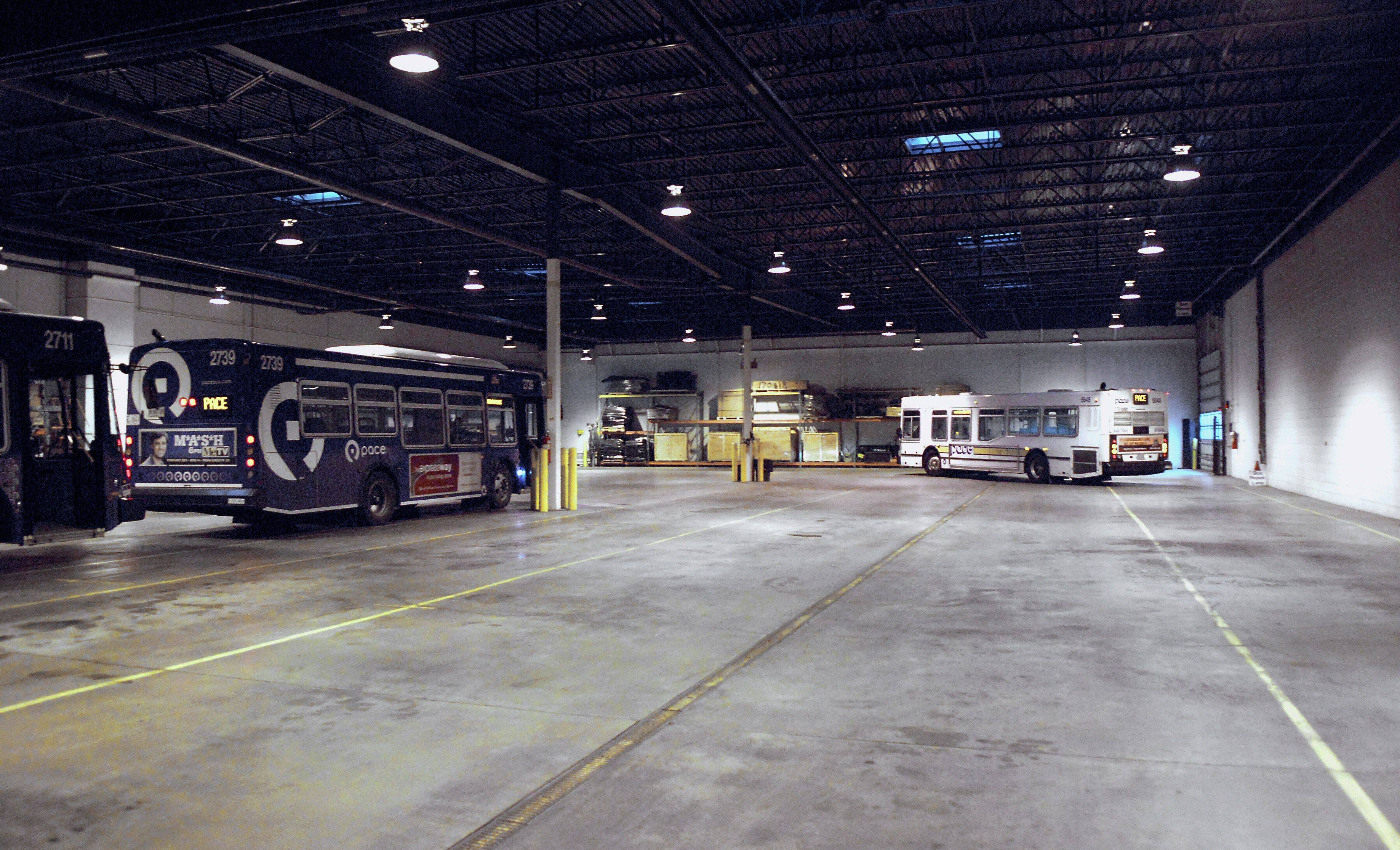 A 35 foot white Pace bus leaves the Elgin garage for the start of its afternoon shift. The blue buses are 30 feet long. At the end of the night, 48 buses will fit inside the garage, which is longer than shown in this photo.