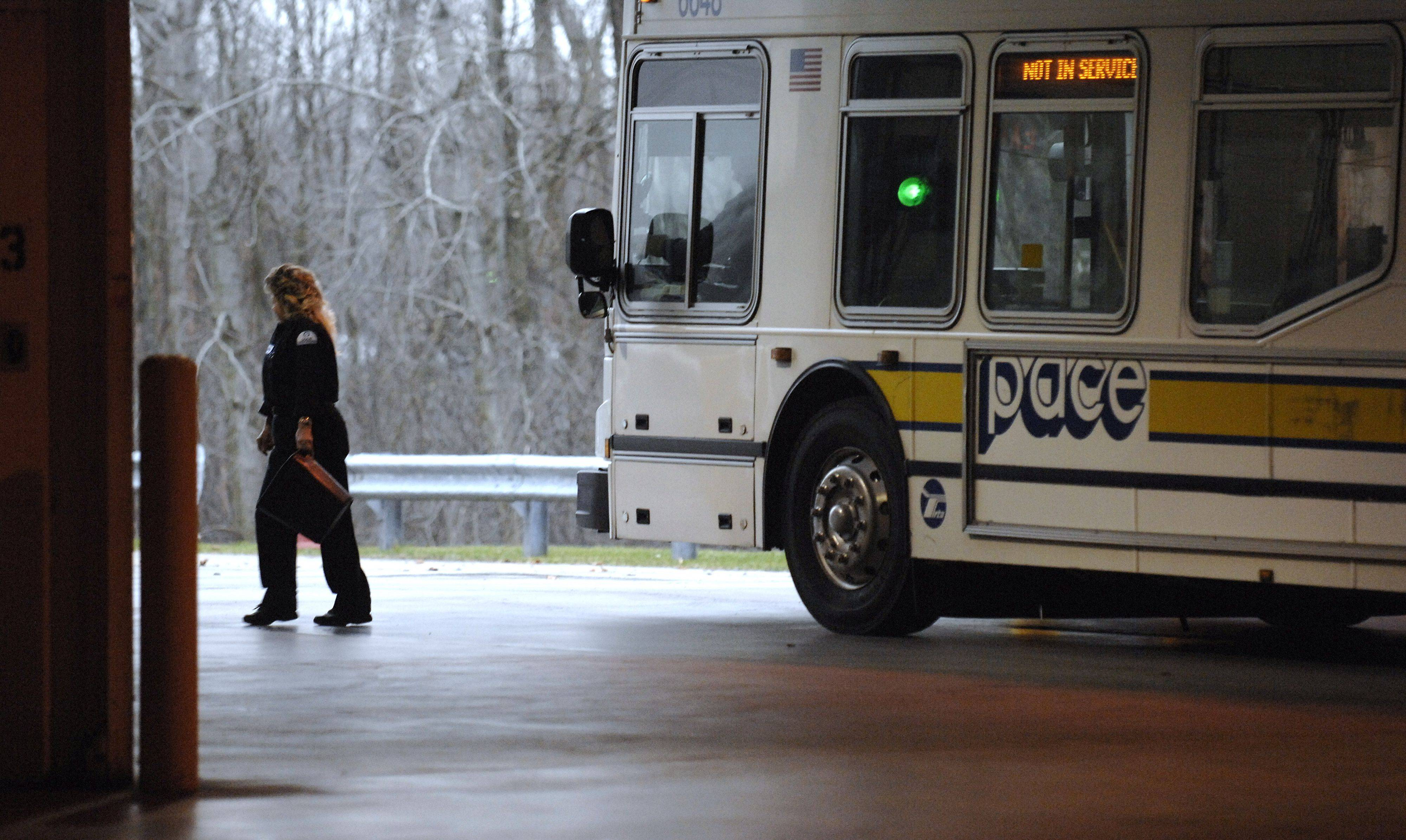 Service worker Audrey Huebner walks away from a bus after talking to the driver departing the Elgin garage for the next shift.