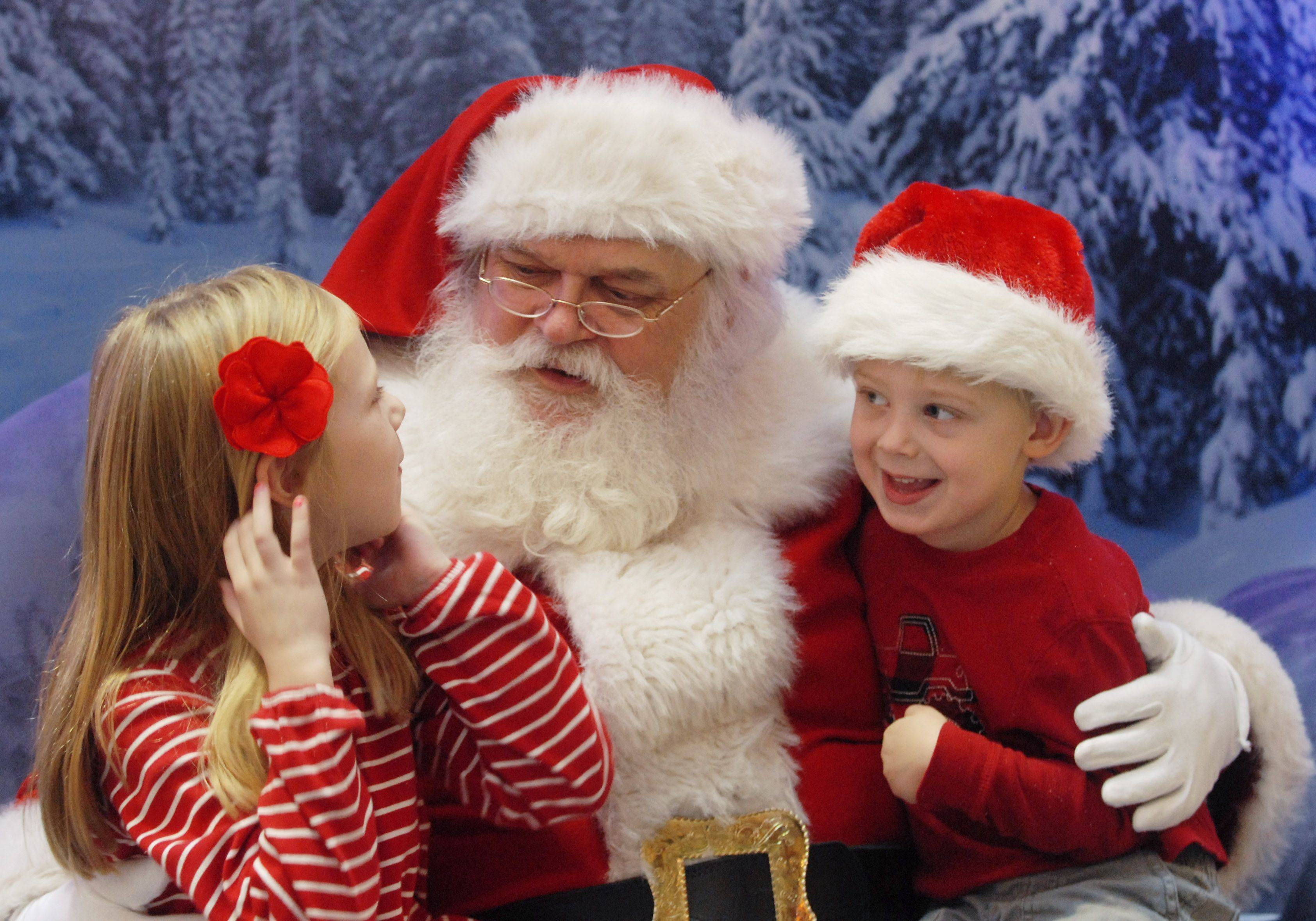 "Julia Olson, 7, and her brother Erick, 4, of Arlington Heights sit with Santa Claus at Woodfield Mall in Schaumburg Thursday. ""I wanted a robot and squinkies"" Julia said afterward, and ""I asked for a racetrack,"" Erick said."