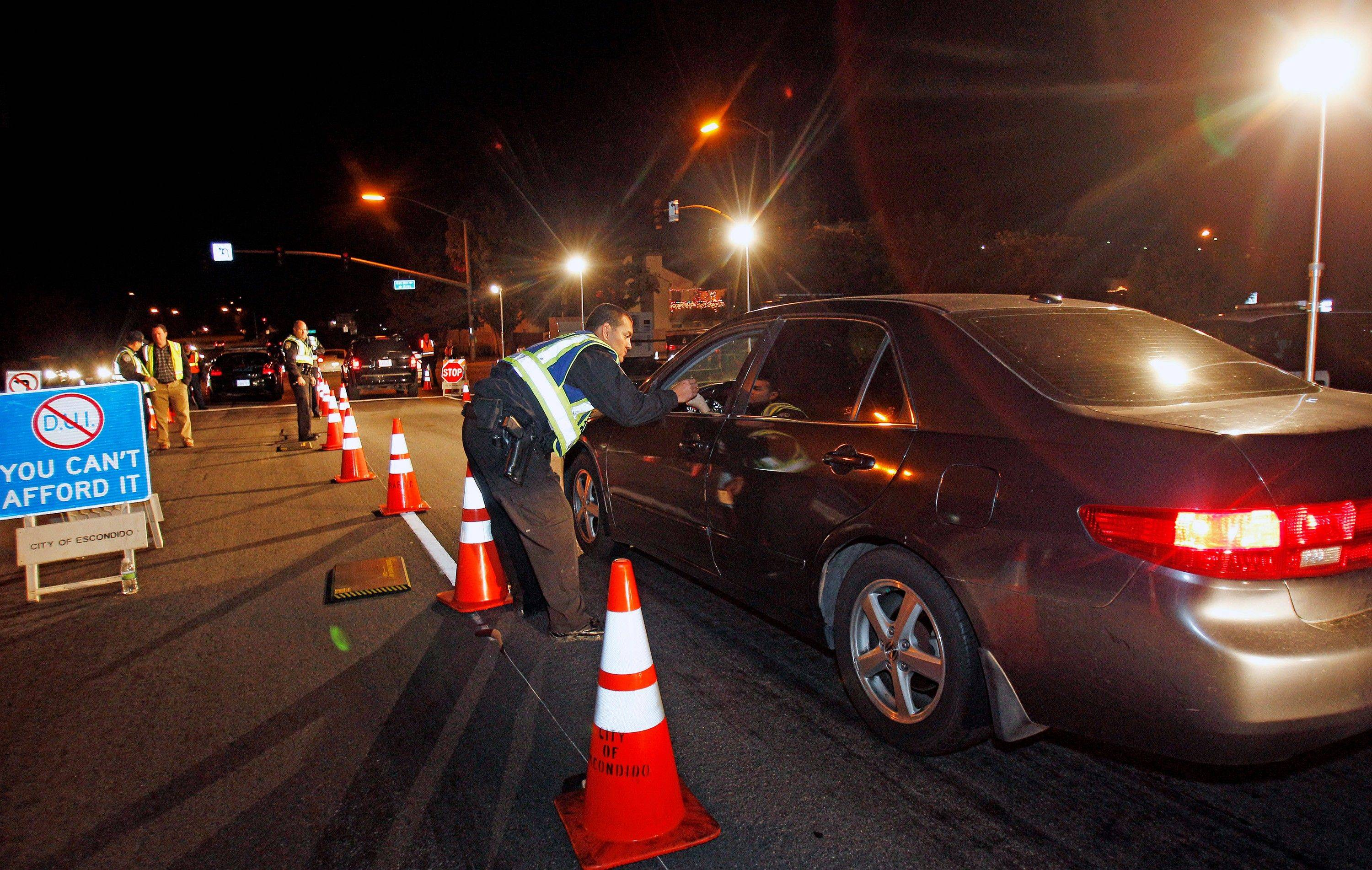 Police officers check drivers at a sobriety checkpoint in Escondido, Calif., on Dec. 16. St