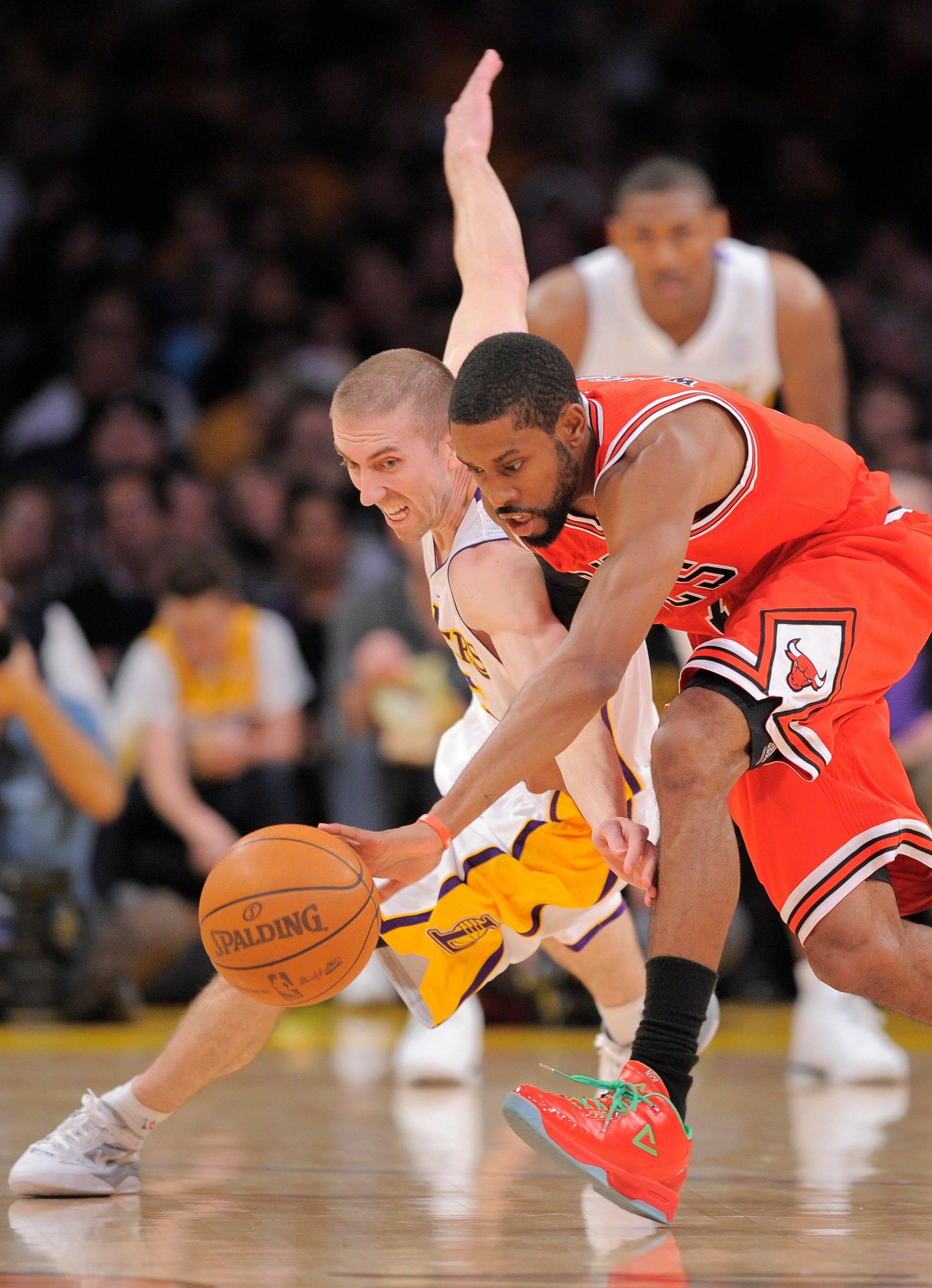 Los Angeles Lakers point guard Steve Blake, left, and Chicago Bulls point guard C.J. Watson go after a loose ball during the first half Sunday in Los Angeles. The Bulls won 88-87.