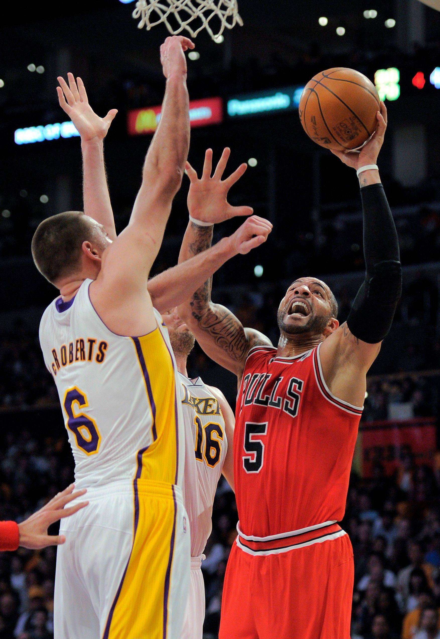 Bulls forward Carlos Boozer puts up a shot as Los Angeles Lakers forwards Josh McRoberts, left, and Pau Gasol defend on Sunday in Los Angeles.