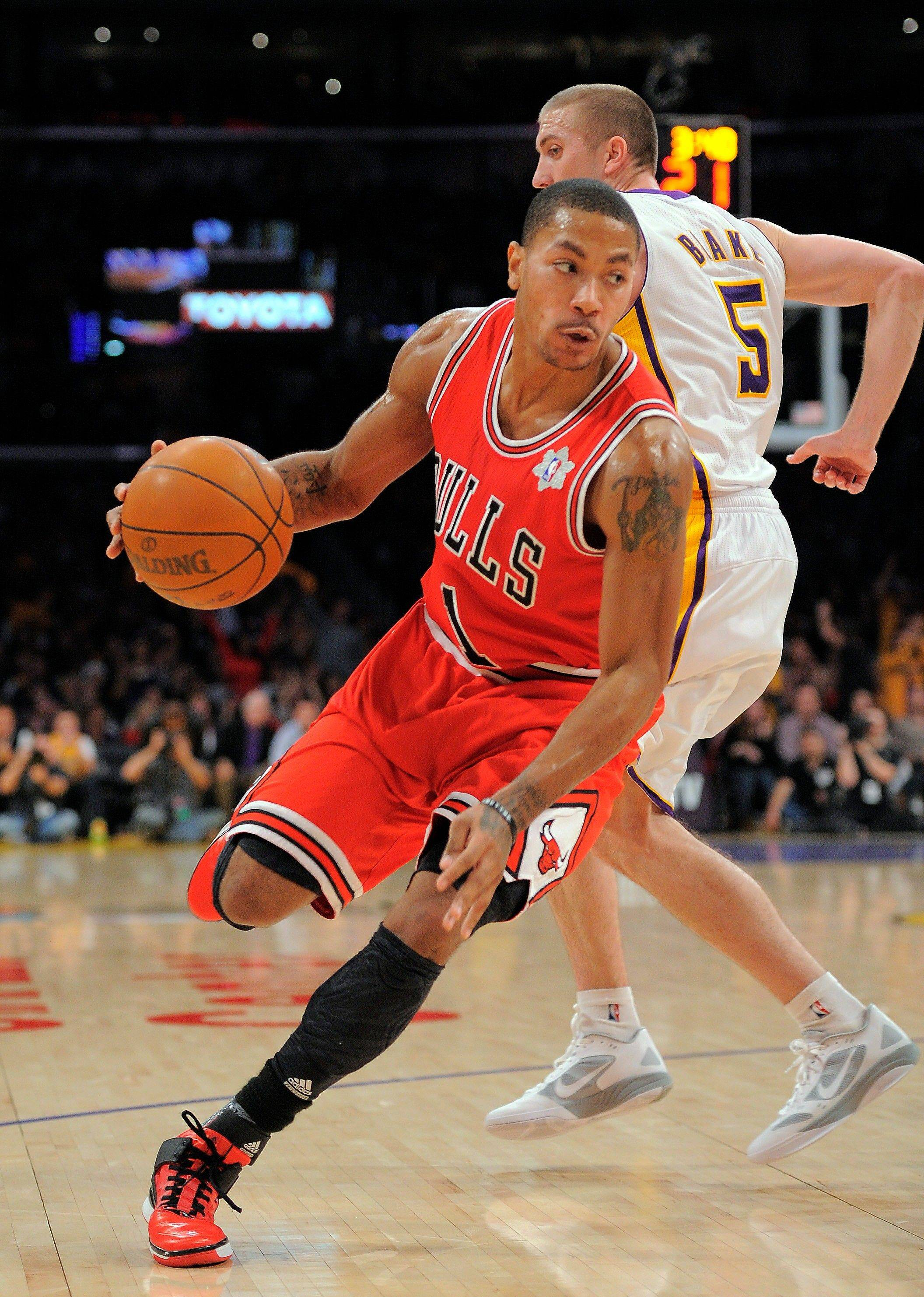 Derrick Rose dribbles past Lakers guard Steve Blake during the second half in Sunday's season opener in Los Angeles.