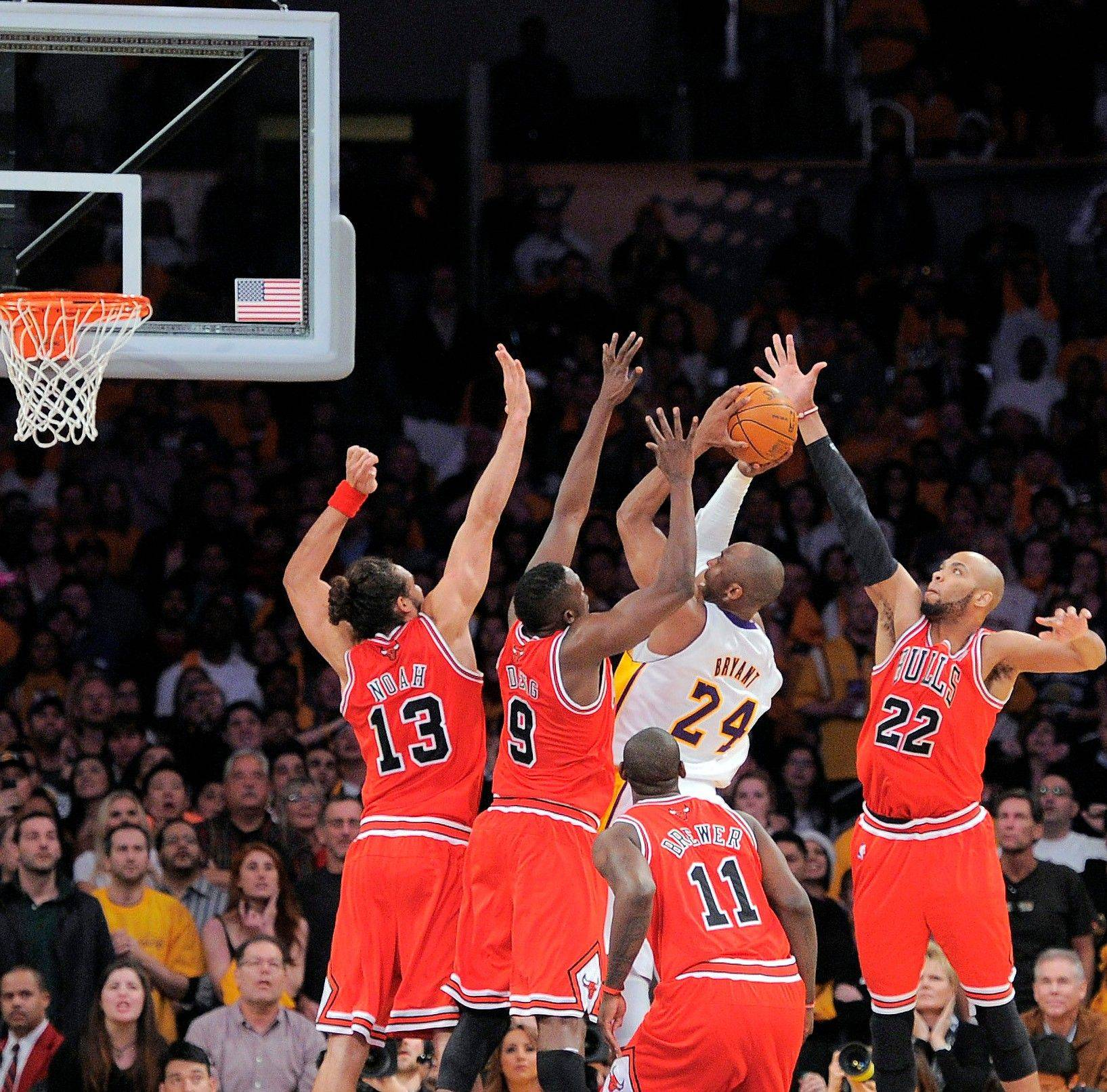 The Lakers' Kobe Bryant (24) tries to take a shot surrounded by Bulls as time expires Sunday. Luol Deng (9) was credited with blocking Bryant's shot to preserve the Bulls' victory.