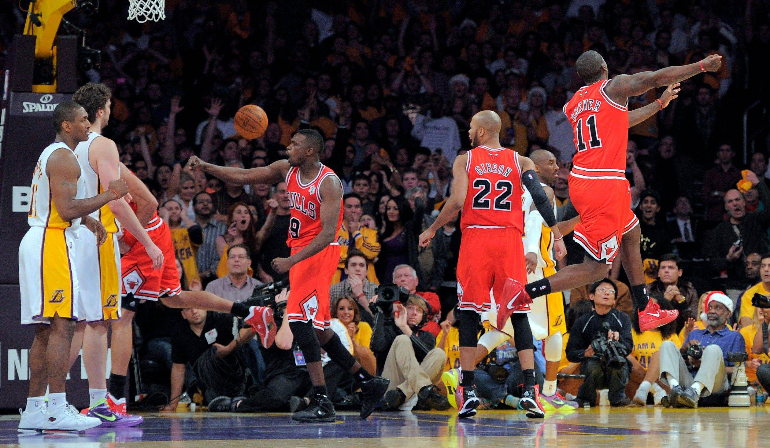 The Bulls' Luol Deng (9), Taj Gibson, (22) and Ronnie Brewer (11) celebrate as time runs out in an 88-87 victory over the Lakers on Sunday in Los Angeles.