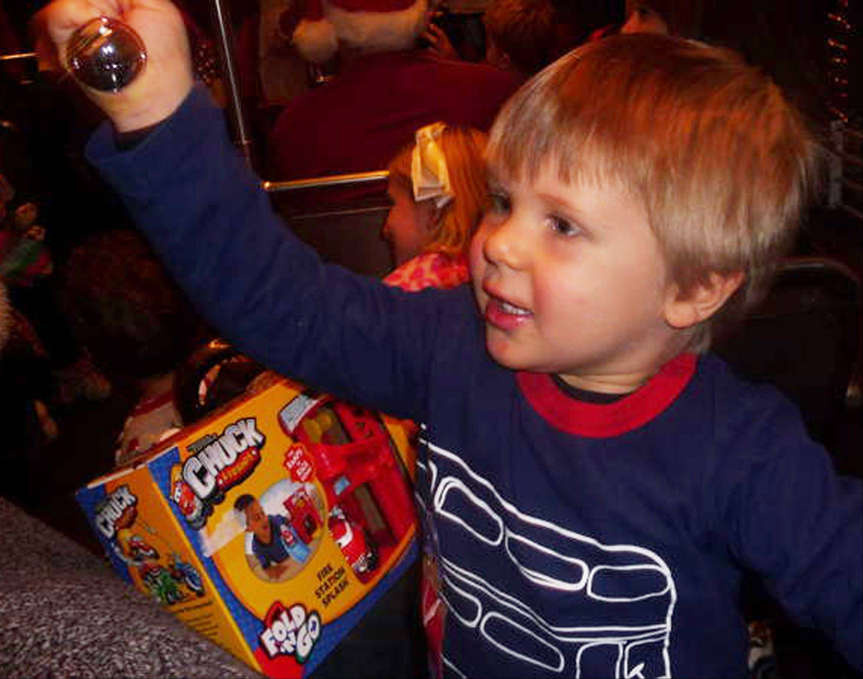 "Noah Lamacki, 2, of Palatine holds the bell he received from Santa at the Batavia Park District's ""Polar Express."""