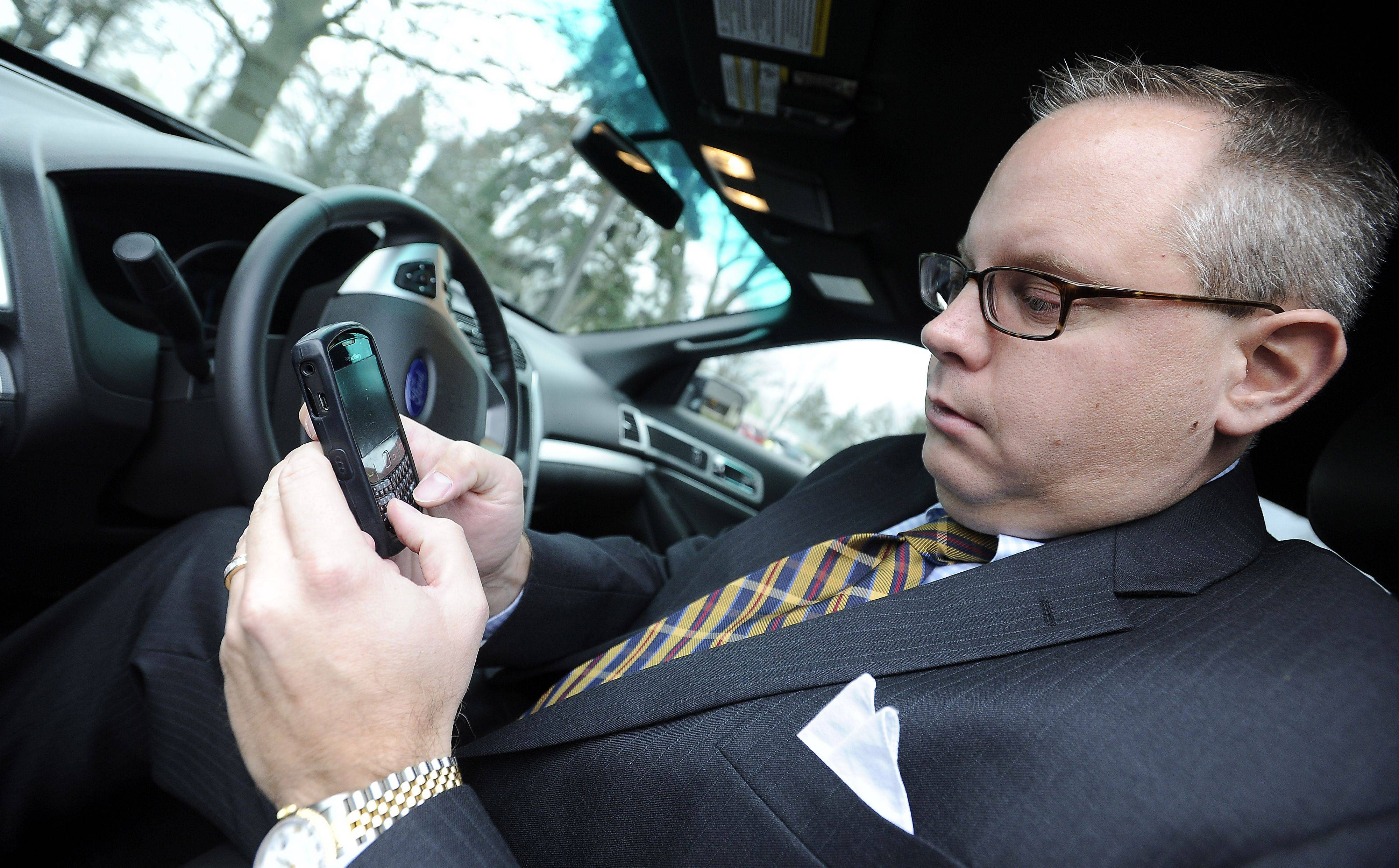 Daniel Chengary, senior account manager at Wheels Inc. in Des Plaines, checks his email before he starts to drive as he is not allowed to make cellphone calls while driving on company time.