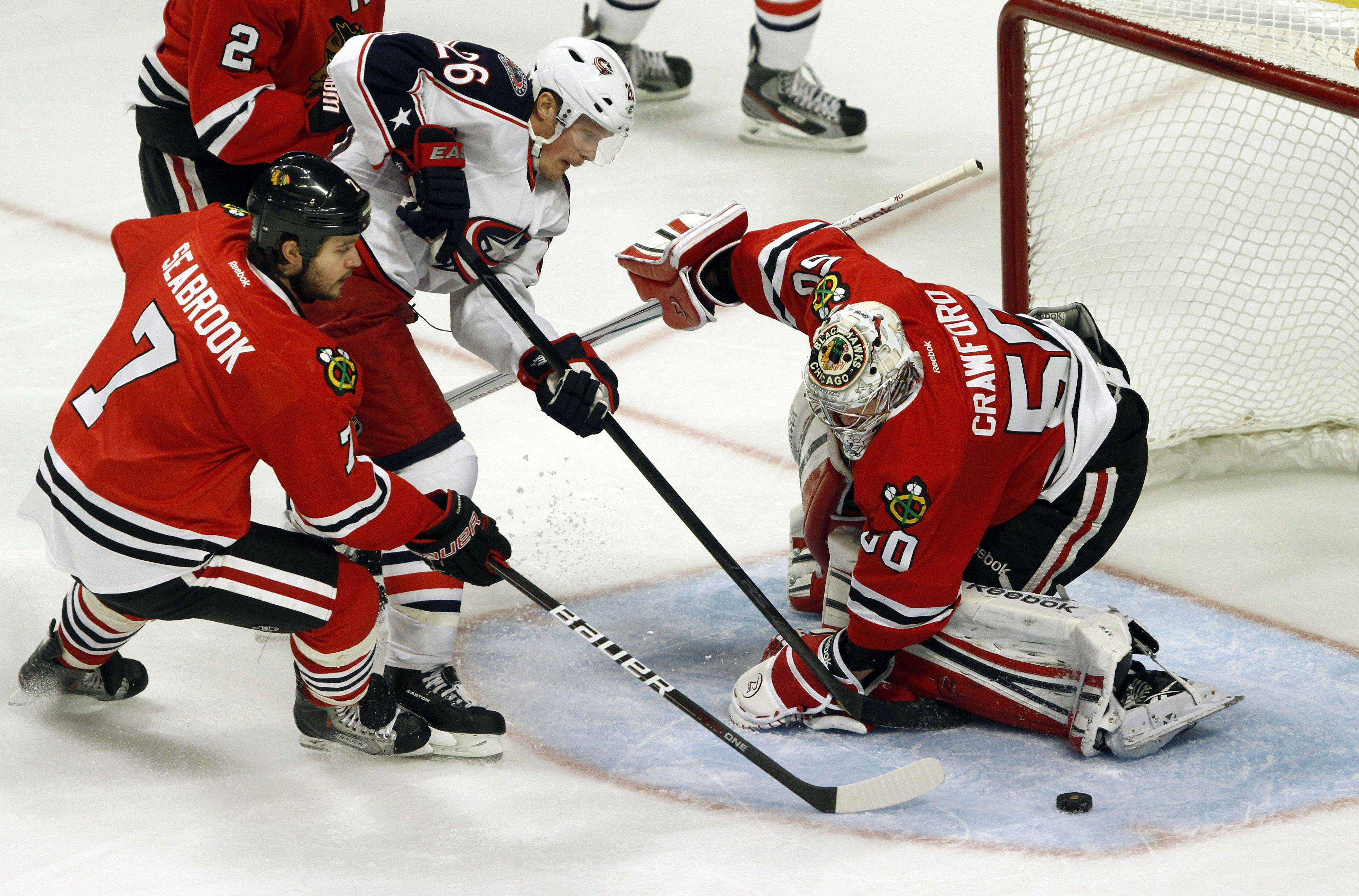 Chicago Blackhawks defenseman Brent Seabrook fights with Columbus Blue Jackets center Samuel Pahlsson as Chicago Blackhawks goalie Corey Crawford makes the save in the third period during their game Monday night at the United Center in Chicago.