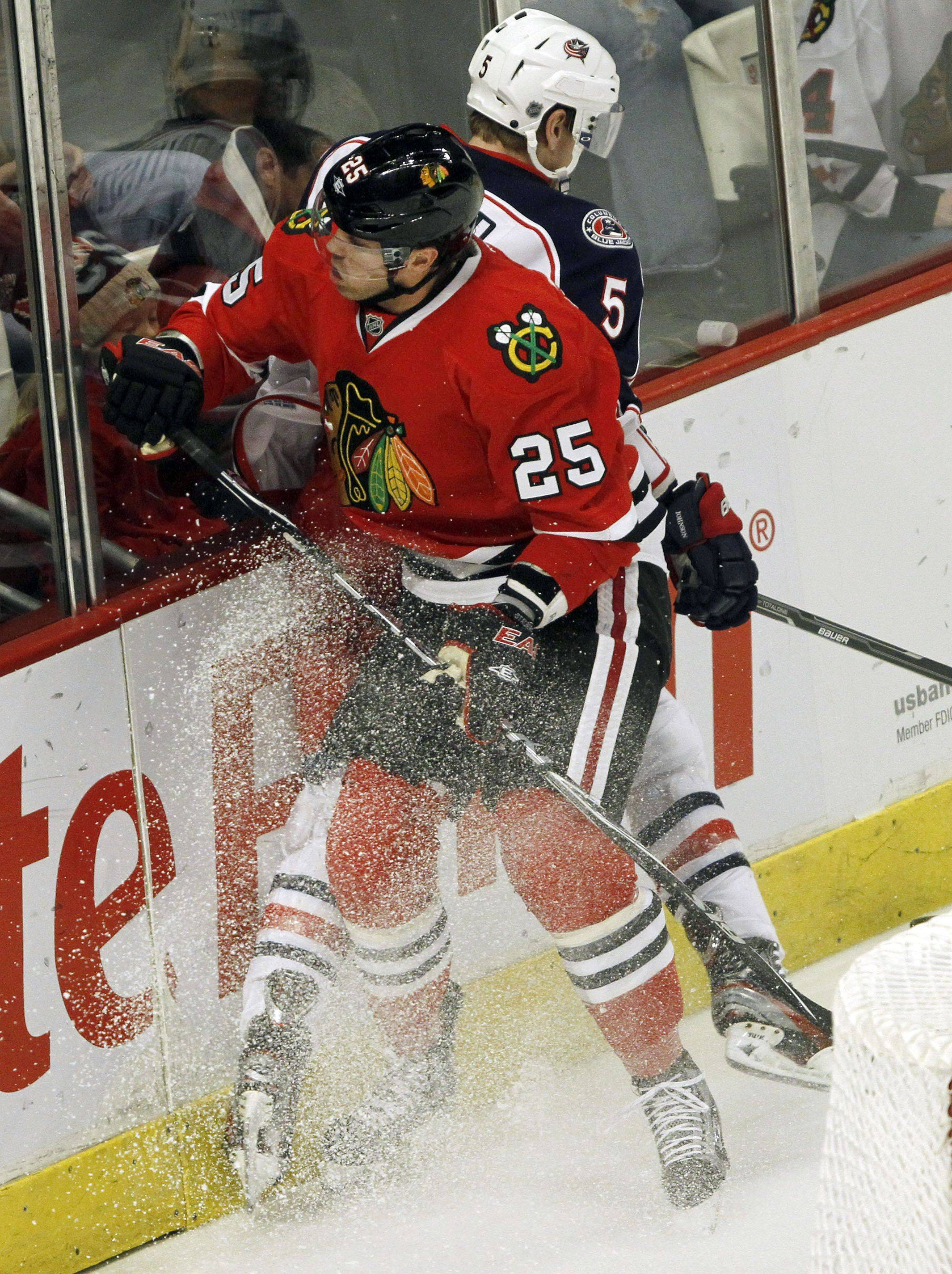 Chicago Blackhawks left wing Viktor Stalberg puts a hit on Columbus Blue Jackets defenseman Aaron Johnson during their game Monday night at the United Center in Chicago.