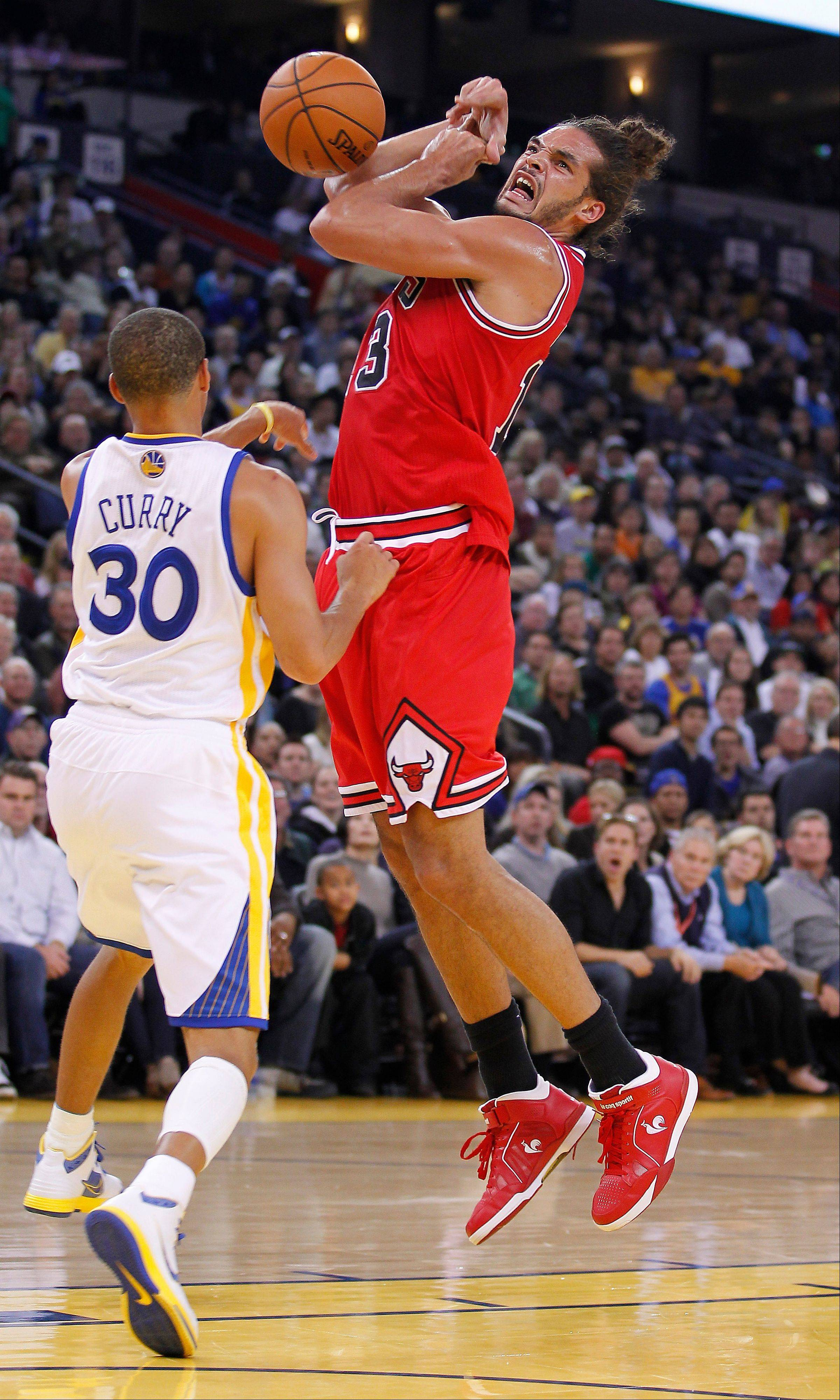 Chicago Bulls' Joakim Noah (13) has the ball stripped by Golden State Warriors' Stephen Curry (30) during the first half of Monday night's game.