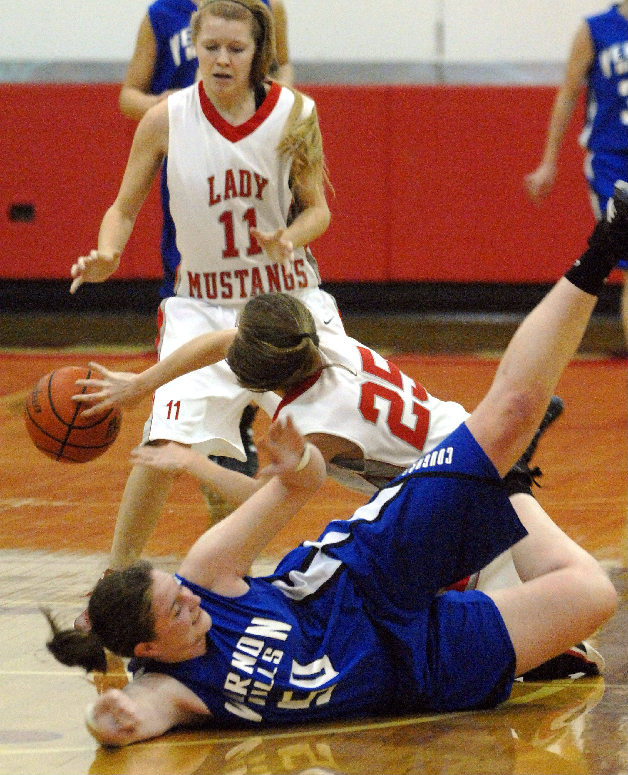 Mundelein's Amanda Davis, 25, passes to teammate Connie Dimick, 11, after reaching a loose ball ahead of Vernon Hills' Meri Bennett-Swanson during Thursday's Lady Mustangs Holiday Classic basketball game in Mundelein.