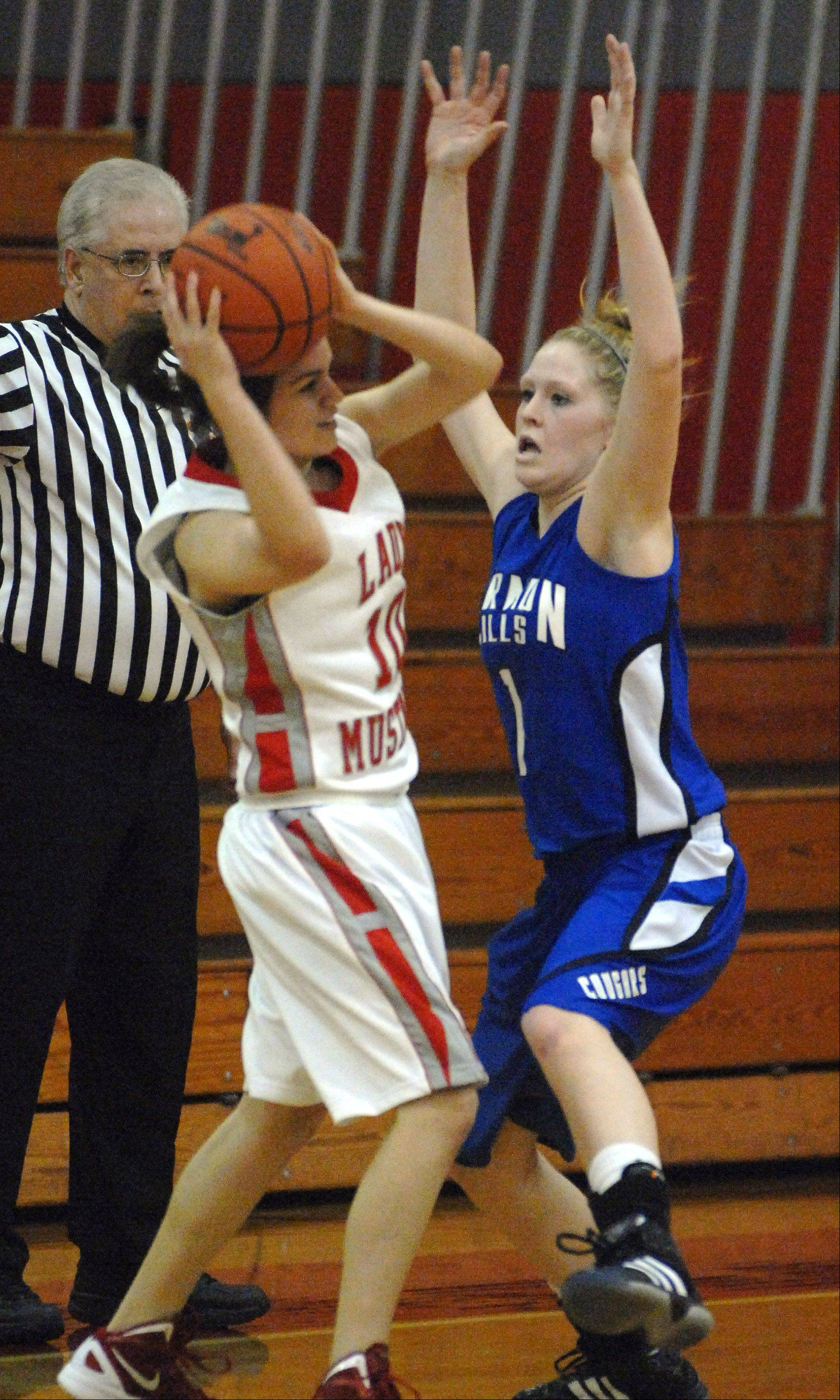 Vernon Hills' Sydney Smith, 1, pressures Mundelein's Kiana Suhling during Thursday's 2011 Lady Mustangs Holiday Classic basketball game at Mundelein High School.