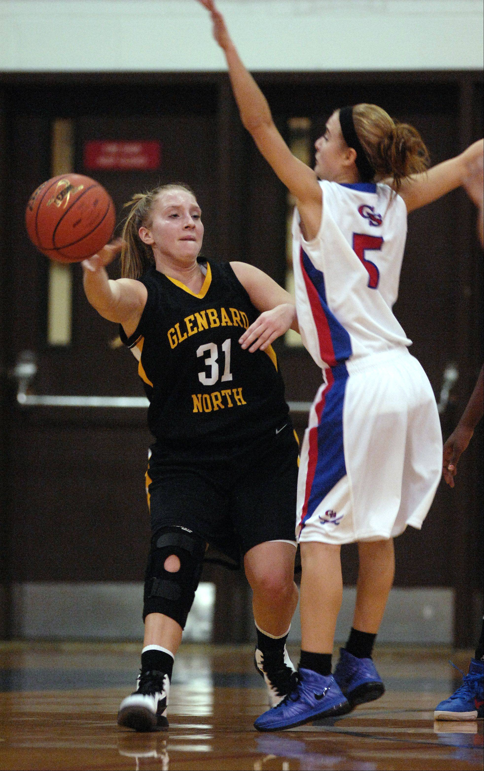 Glenbard North's Amy Flason passes around Glenbard South's Theresa Scheet during Tuesday's girls basketball game in Glen Ellyn.