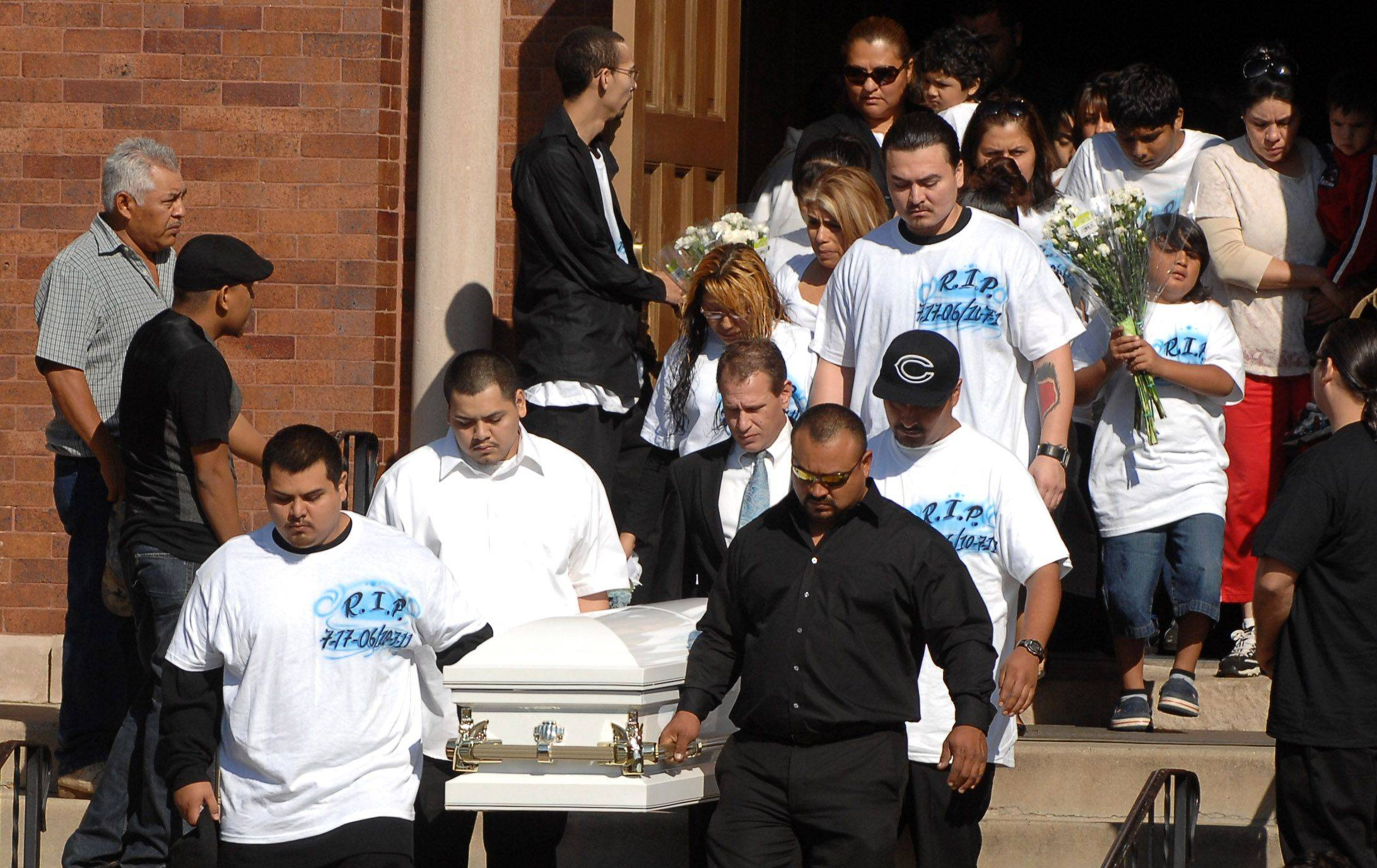 Pallbearers carry out the casket following the funeral for Eric M. Galarza Jr., 5, at St. Joseph Catholic Church. The boy was killed in a gang-related shooting in Elgin. His parents, Eric and Denisse, are following behind the casket.