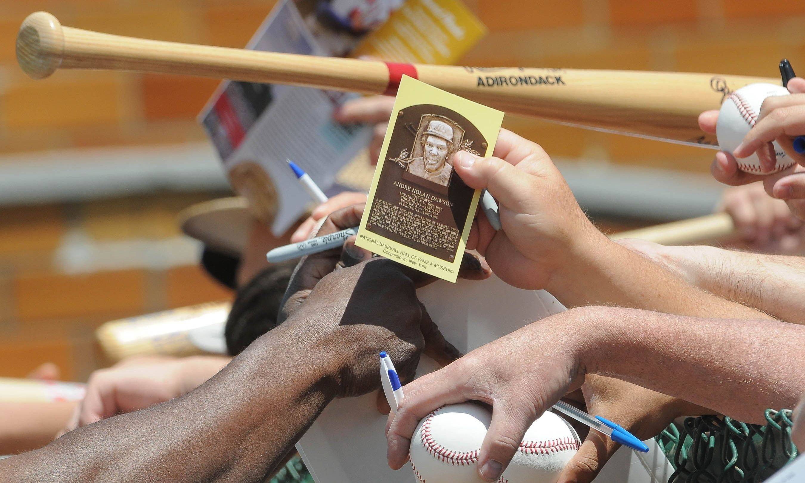 Fans reach to get Andre Dawson's autograph before the Hall of Fame Classic baseball game at Doubleday Field in Cooperstown, N.Y. last June.
