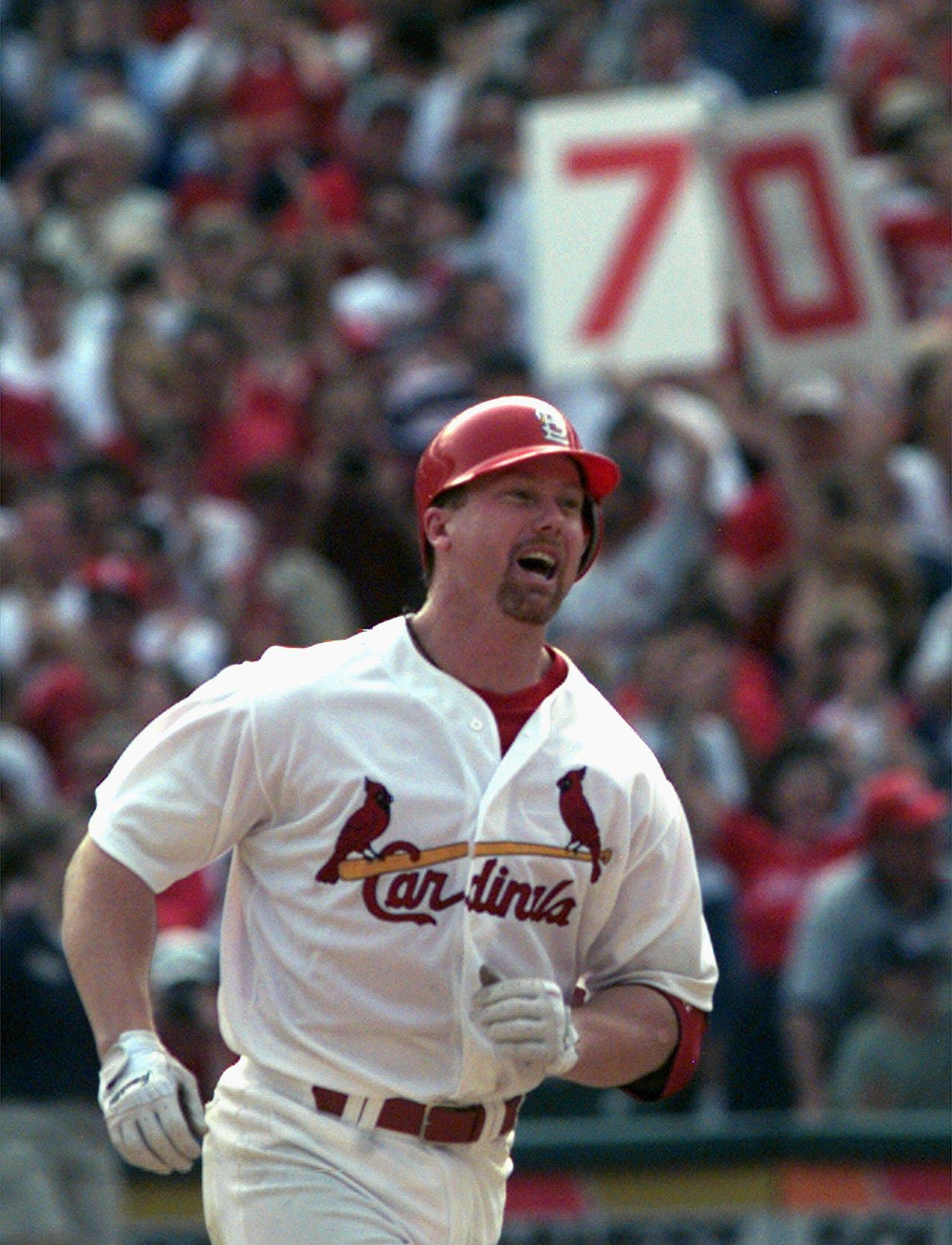 ** ADVANCE FOR WEEKEND EDITIONS, MARCH 19-20 - FILE - ** This Sept. 27, 1998, file photo shows St. Louis Cardinals slugger Mark McGwire smiling as he rounds the bases after hitting his 70th home run of the season in the seventh inning against Montreal Expos pitcher Carl Pavano, at Busch Stadium in St. Louis. The steroids-era whipping boy is undiminished among those who appreciate his historic season more than a dozen years ago.