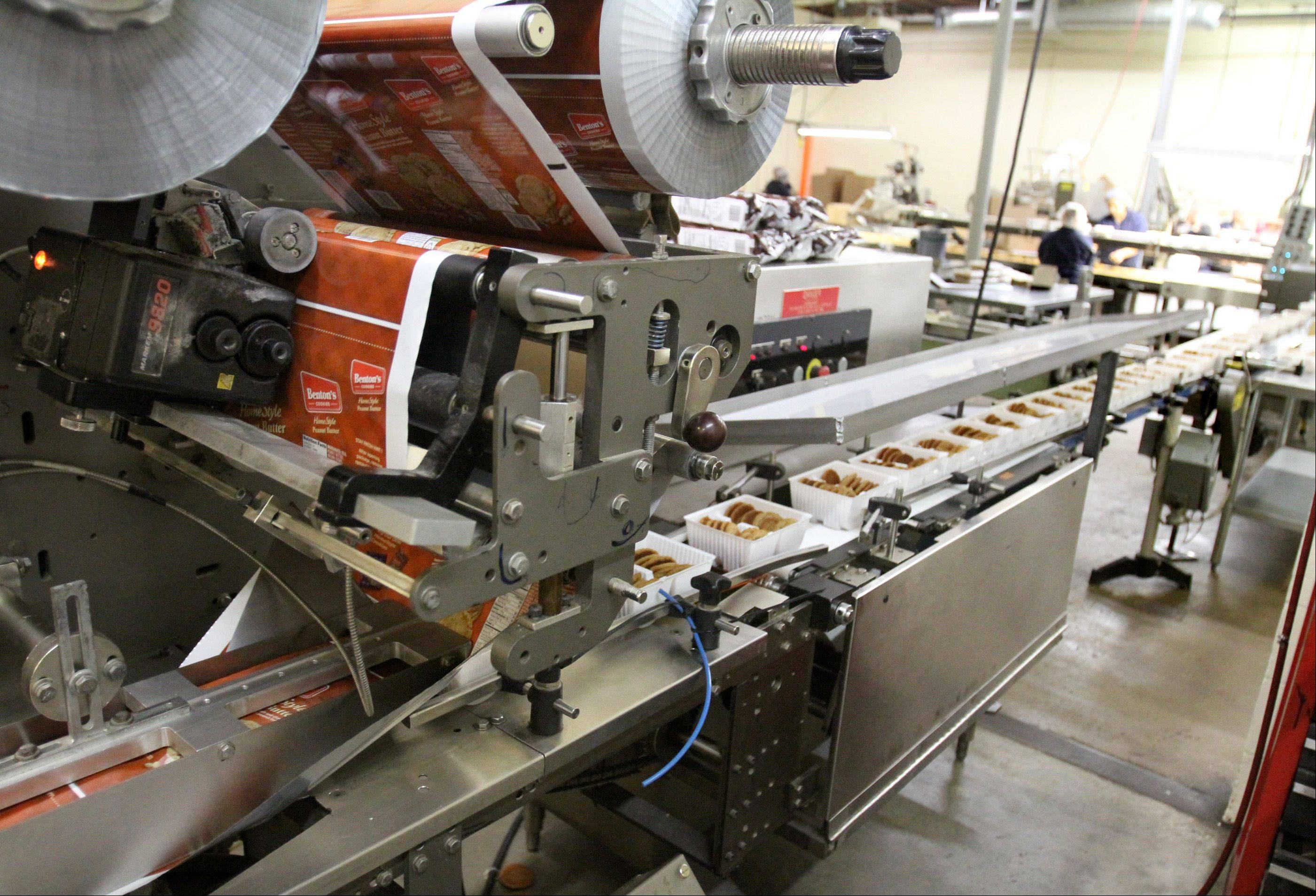 A machine wraps some of the 25,000-pounds of cookies packaged each day, including cookies under different brand names shown on labels here.