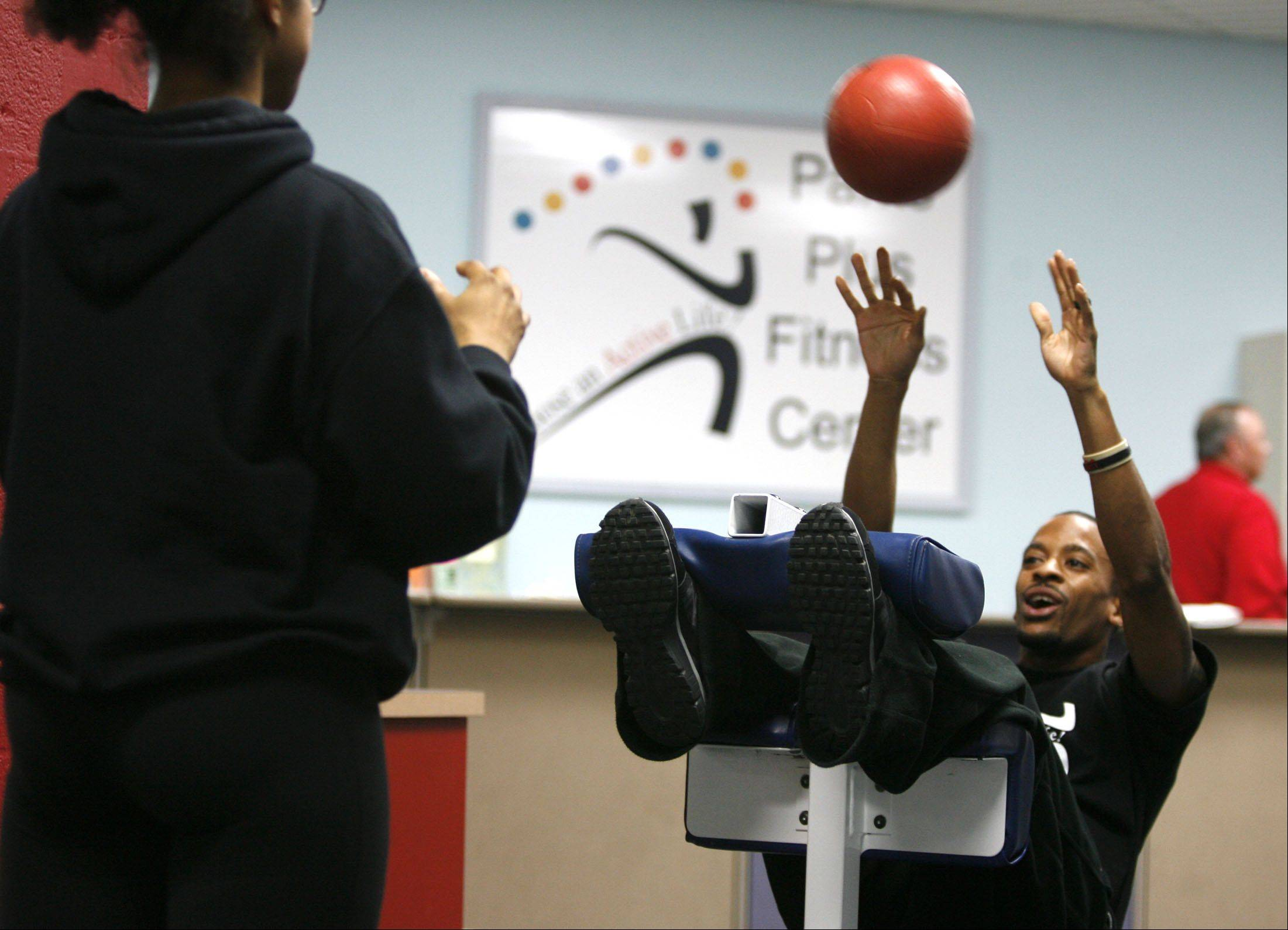 Personal trainer Michelle Artist tosses a medicine ball with trainer Will Lofton, performing an abdominal exercise at the Wheaton Park District's Parks Plus Fitness Center. Free exercise classes and consultations with trainers are available Saturday, Jan. 7 through Monday, Jan. 9.