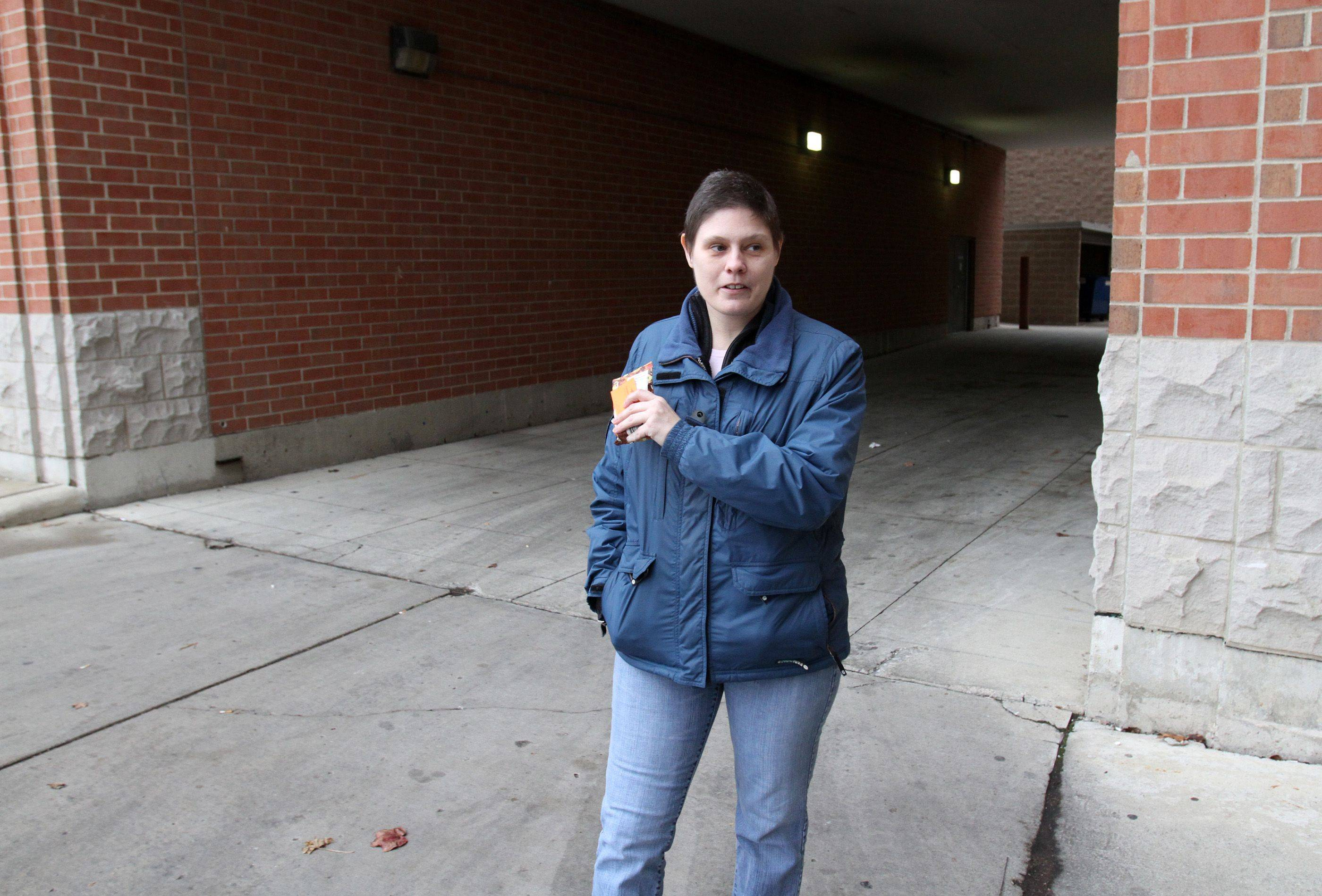 AnnMarie Walsh points out the concrete area, on far right, in the alley near the Vail Avenue parking garage in downtown Arlington Heights where she slept in her sleeping bag during months shelters were not open. Walsh said condominium building residents and retail store owners would leave her food.