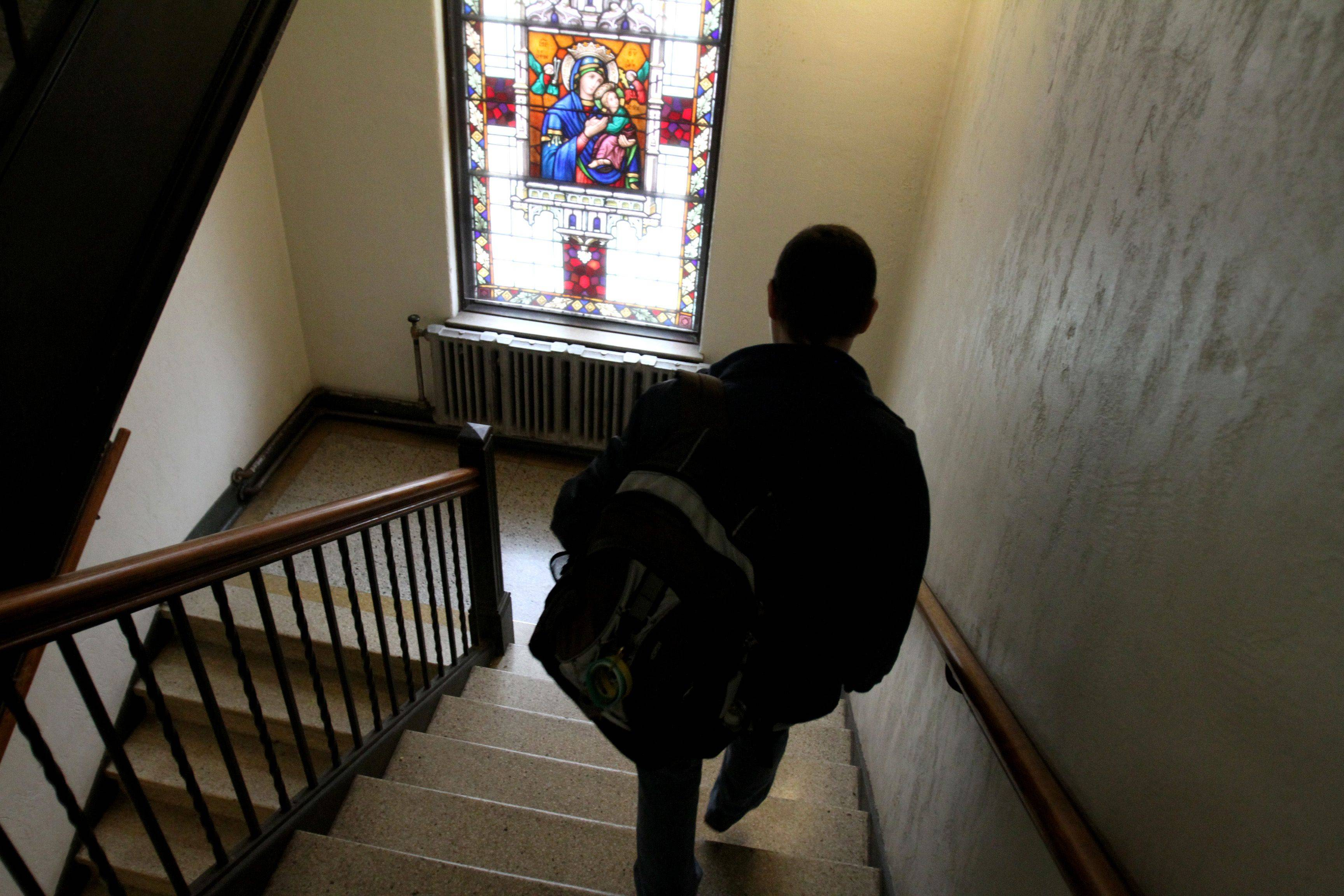 AnnMarie Walsh walks down the stairs from her second floor room at Deborah's Place in Chicago. The residence was formerly a convent.
