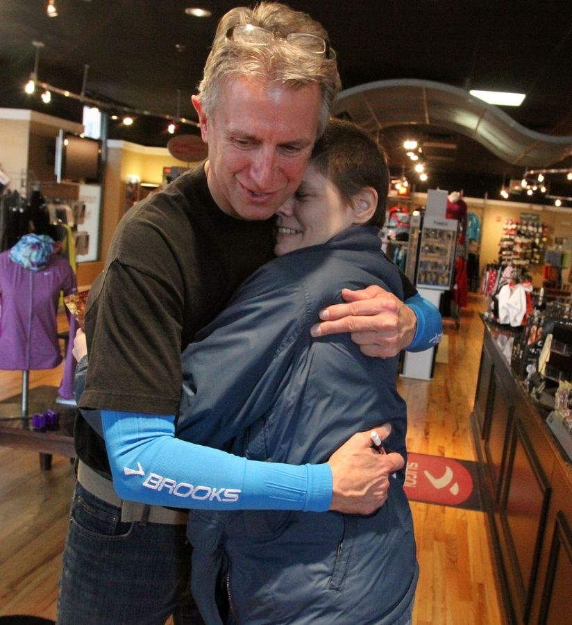 AnnMarie Walsh gets a hug while visiting Mark Rouse, owner of Runners High 'n Tri. For a few years, a homeless Walsh slept in an alley behind the store in downtown Arlington Heights. She said Rouse sometimes placed a bottle of water and an energy bar next to her as she slept.