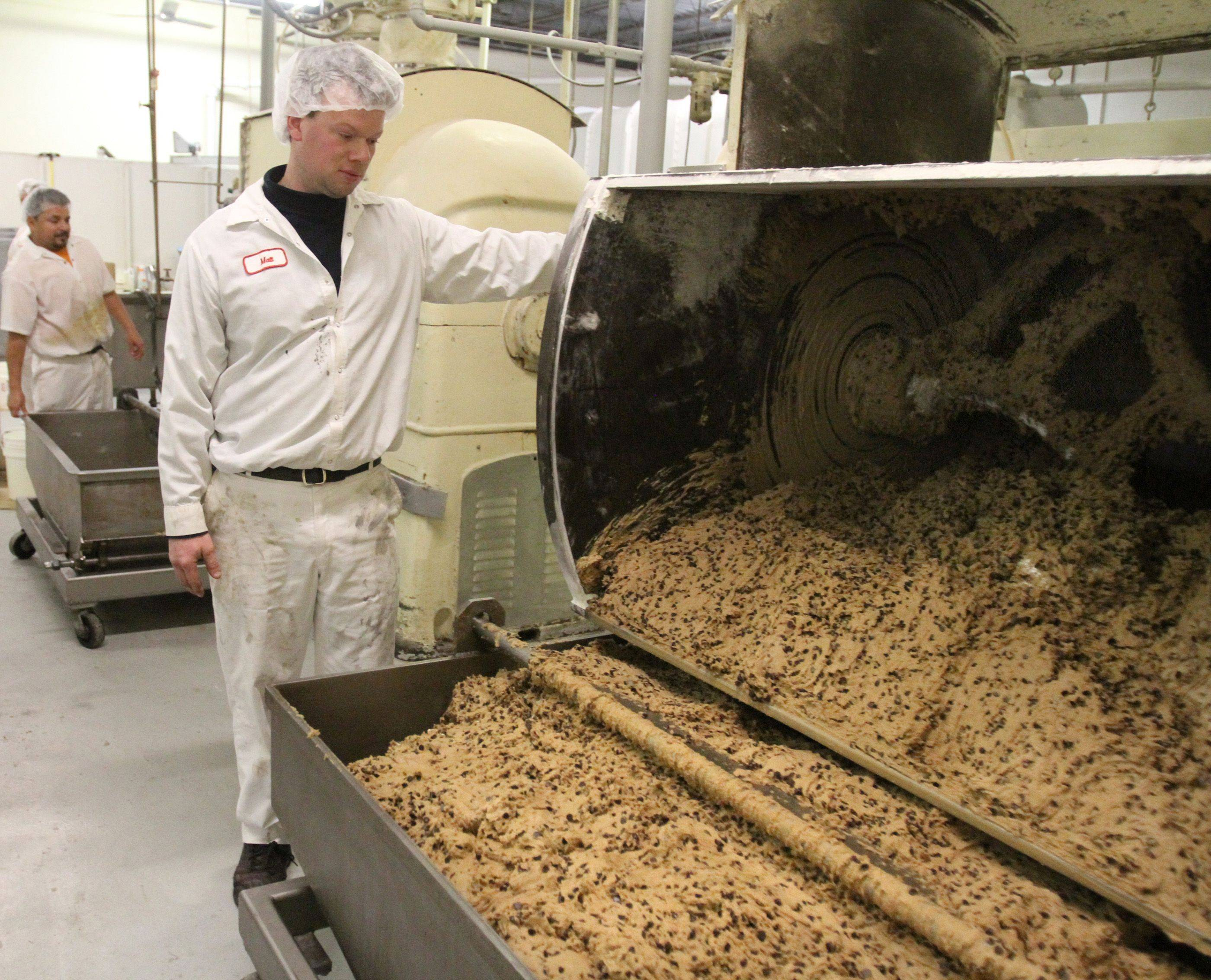 Matt Pierce mixes raw chocolate chip cookie dough in one of the two giant mixers. The company uses about 700,000 pounds of chocolate each year.