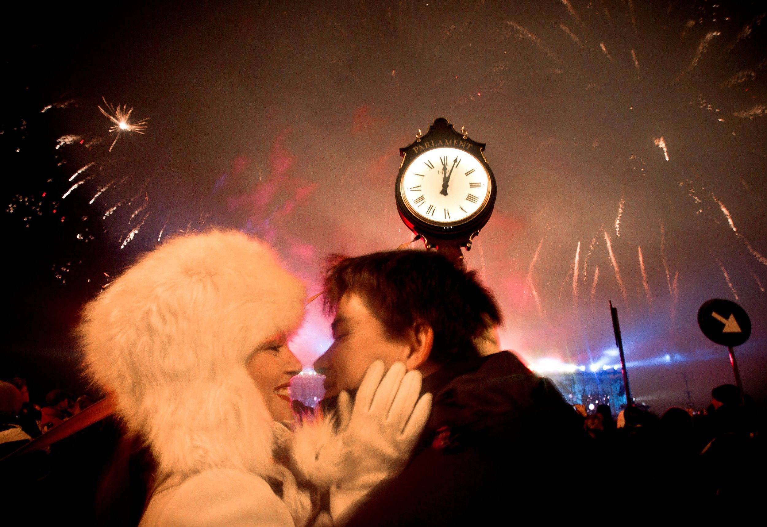 A couple kiss as fireworks explode in the sky over Bucharest, Romania, at midnight, Sunday, Jan. 1, 2012, during street celebrations of the new year. Large crowds gathered downtown Romania's capital taking advantage of the dry weather to attend the celebrations.