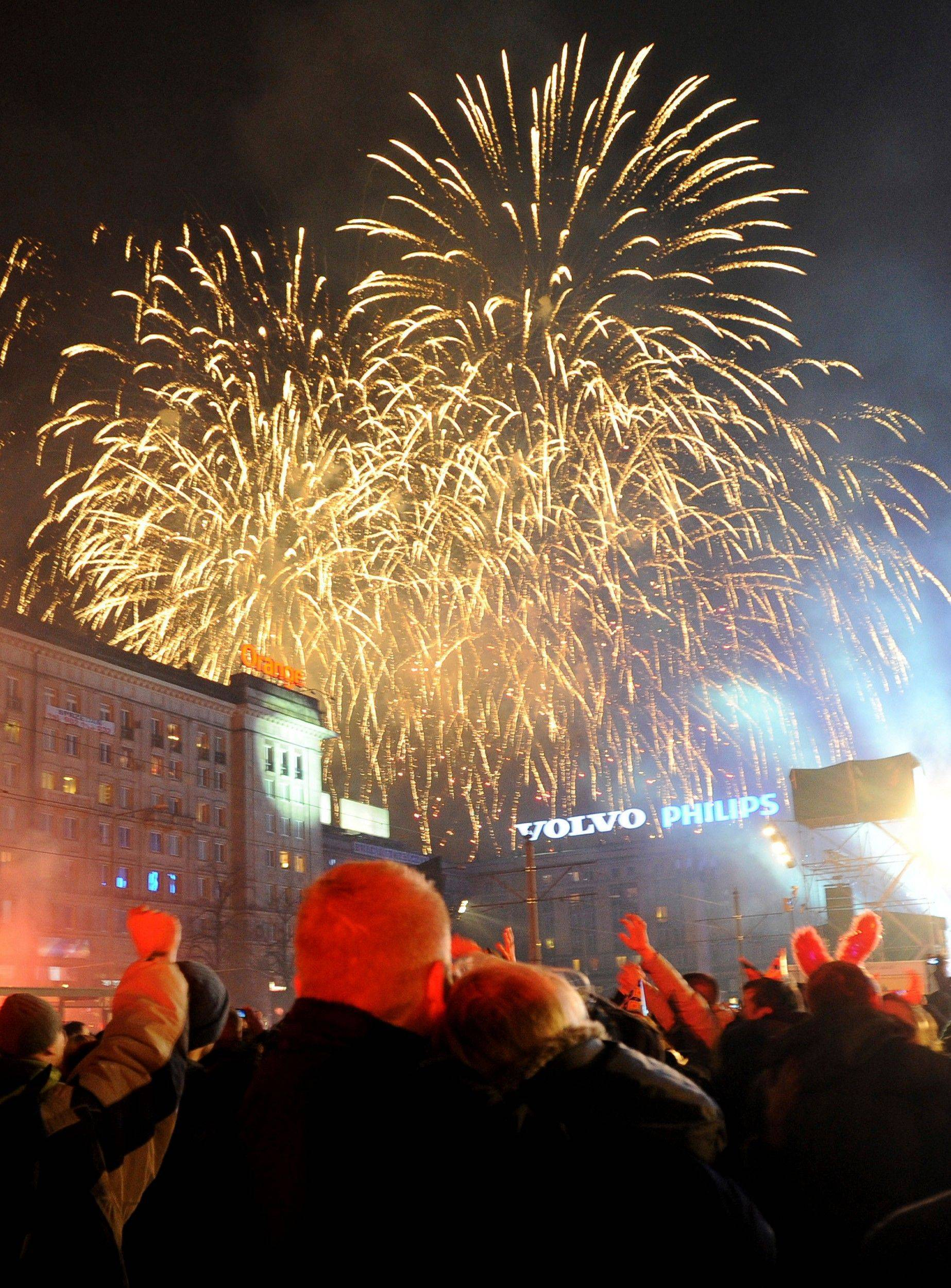 People watch fireworks as they welcome the New Year at the Constitution Square in Warsaw, Poland, Sunday, Jan. 1, 2012.