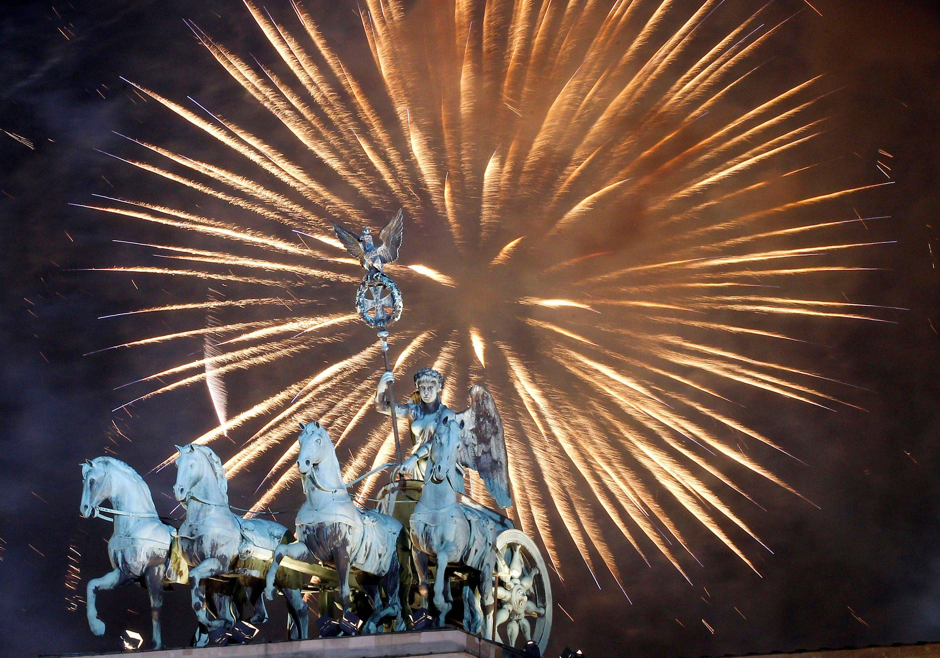 Fireworks light the sky above the Quadriga at the Brandenburg Gate in Berlin shortly after midnight, greeting the New Year, Sunday, Jan. 1, 2012. Hundred thousands of people celebrated the beginning of the New Year 2012 in Germany's capital.