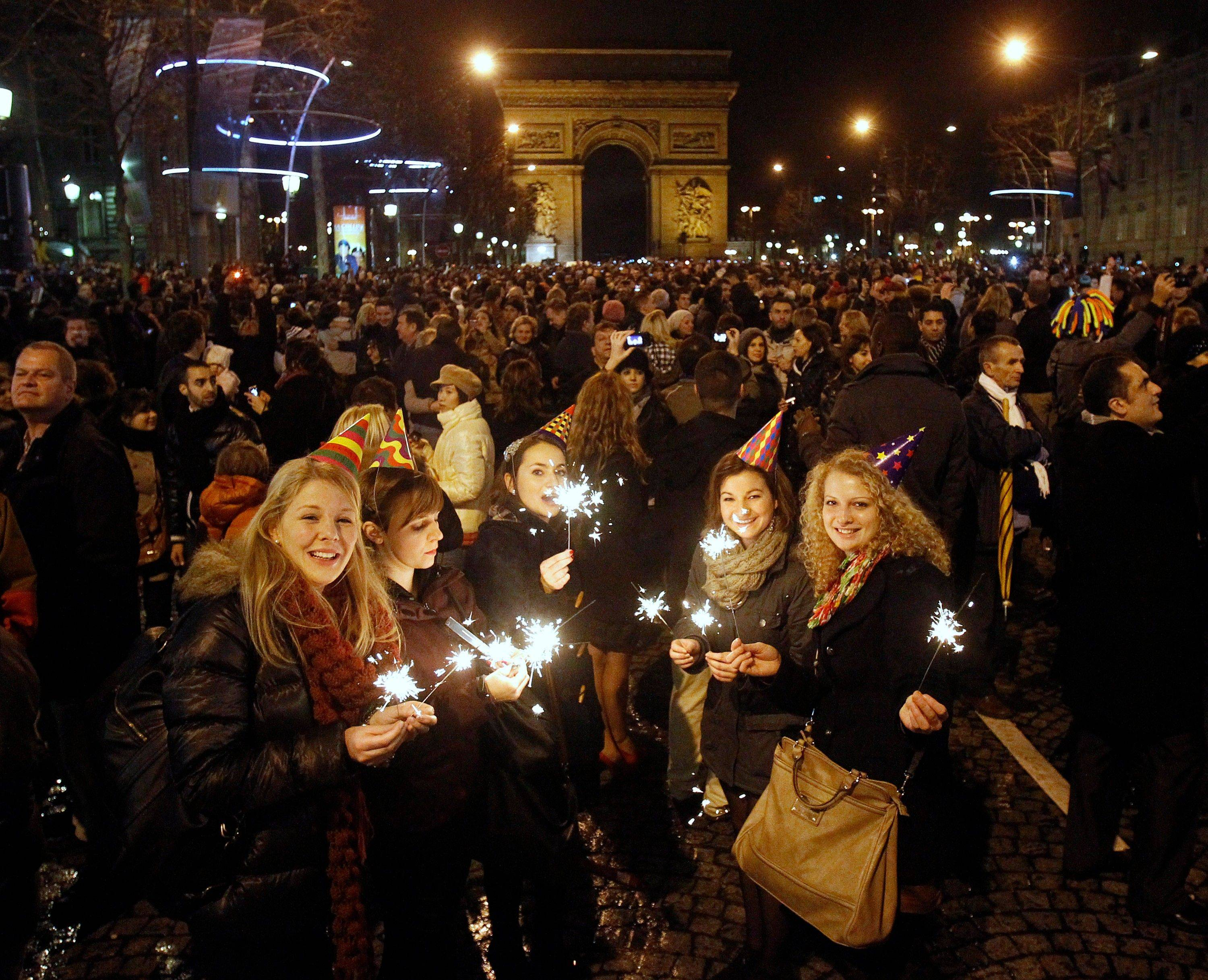 Revelers celebrate the New Year on the Champs Elysees avenue in Paris, Sunday Jan. 1, 2012. Visible in background is the Arc de Triomphe.