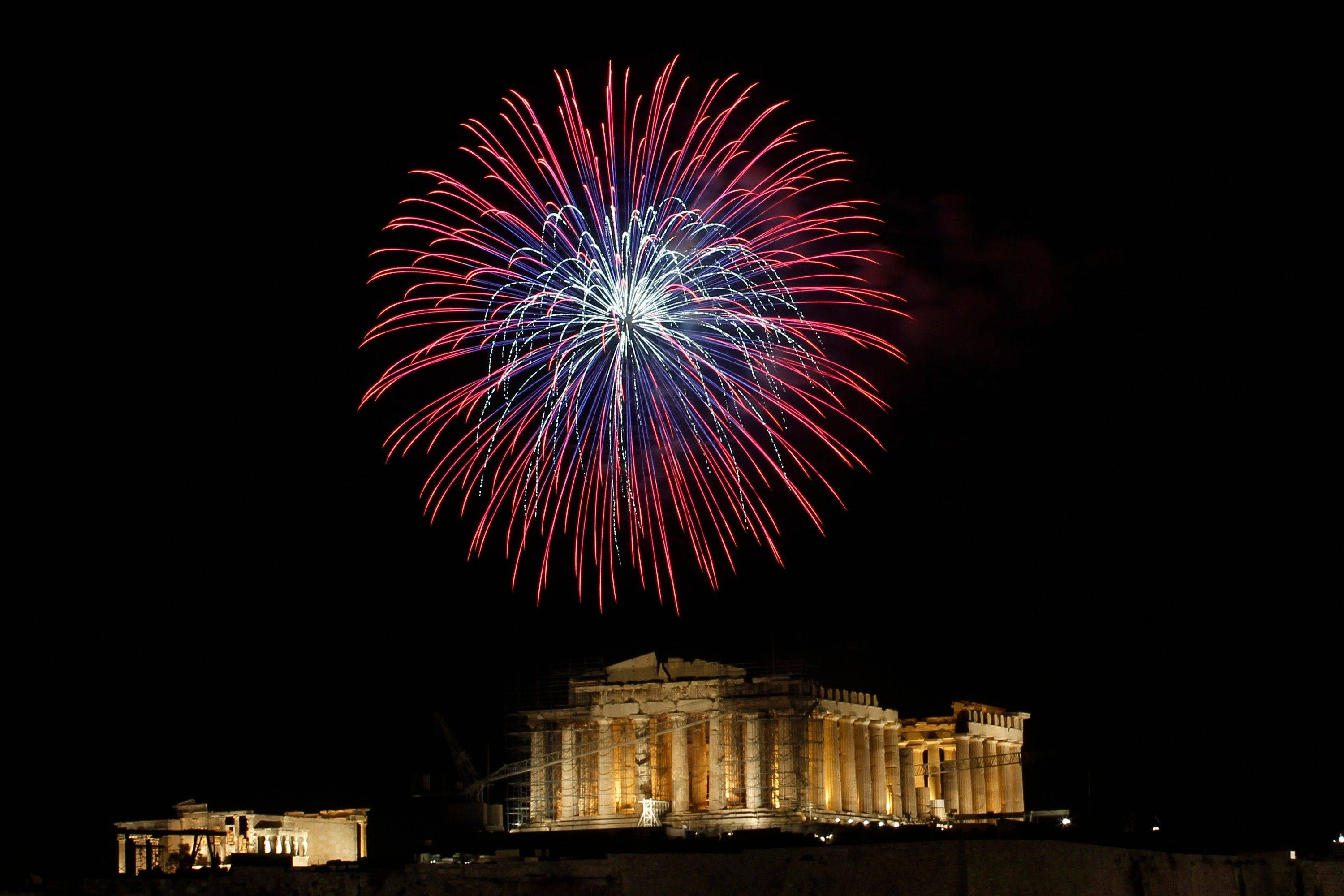 Fireworks explode over the ancient Acropolis Hill with the Parthenon temple during the New Year's celebrations in Athens, on Sunday, Jan. 1, 2012.