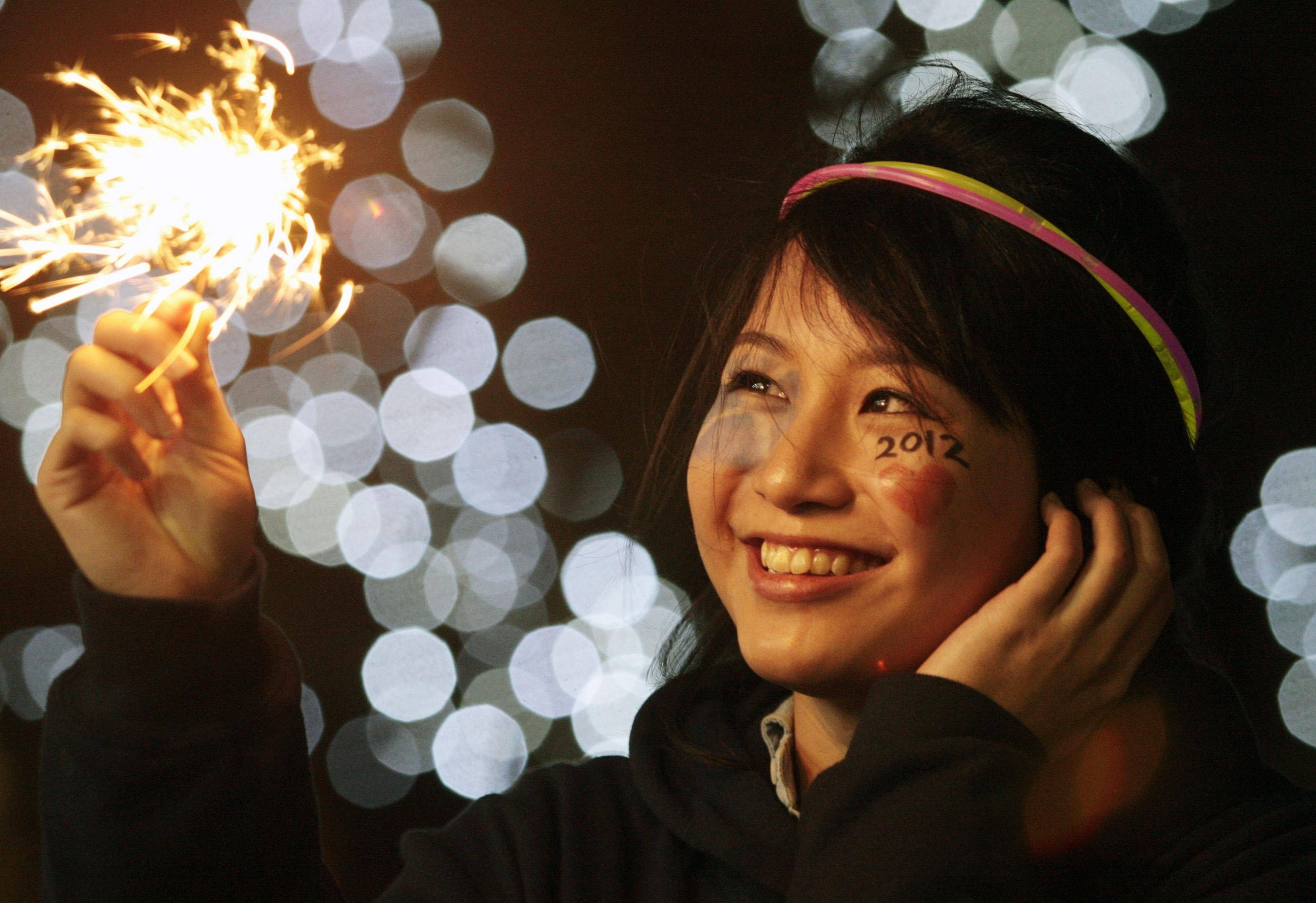 Jessica Ong from Singapore starts her new year celebrations early on New Year's Eve, at the Hogmanay street party on Princes Street, Edinburgh, Scotland, Saturday Dec. 31, 2011.