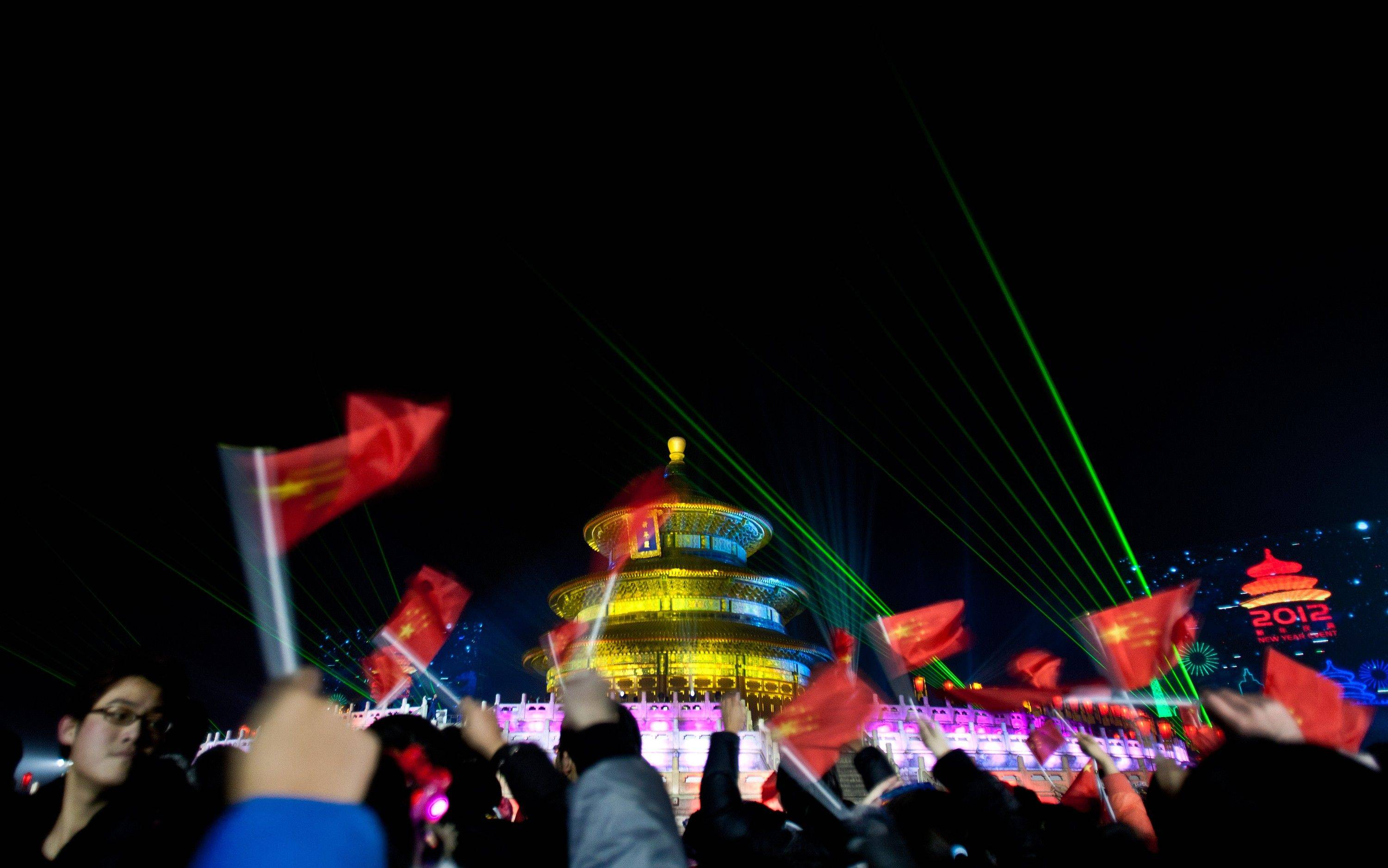 Visitors waves China national flags as they celebrate a light show at the Temple of Heaven during the New Year Countdown Ceremony in Beijing, China, Sunday Jan. 1, 2012.