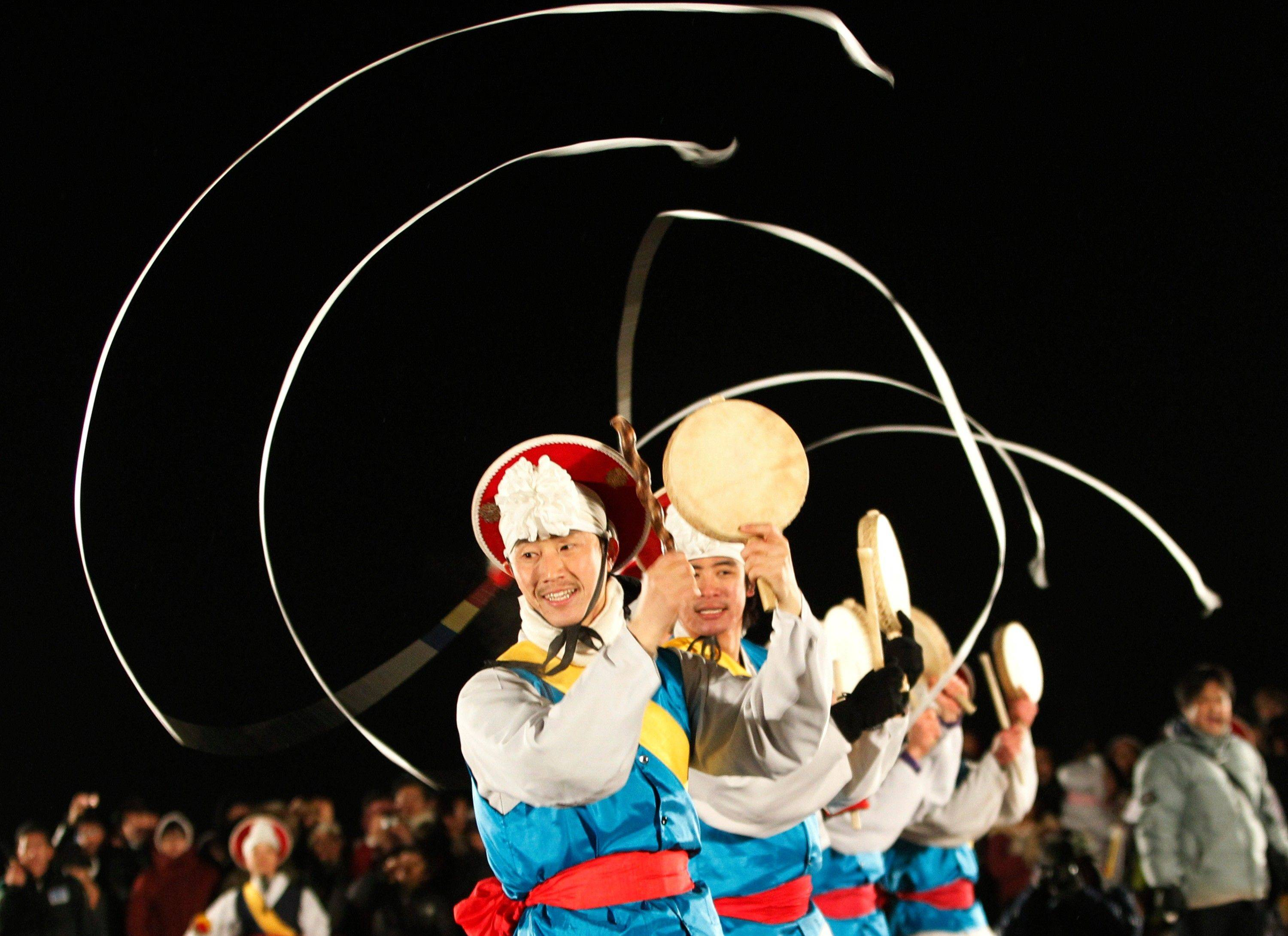 South Koreans in traditional costumes perform to celebrate the New Year near the border village of Panmunjom (DMZ) that separates the two Koreas since the Korean War, at Imjingak Pavilion in Paju, South Korea, Sunday, Jan. 1, 2012.